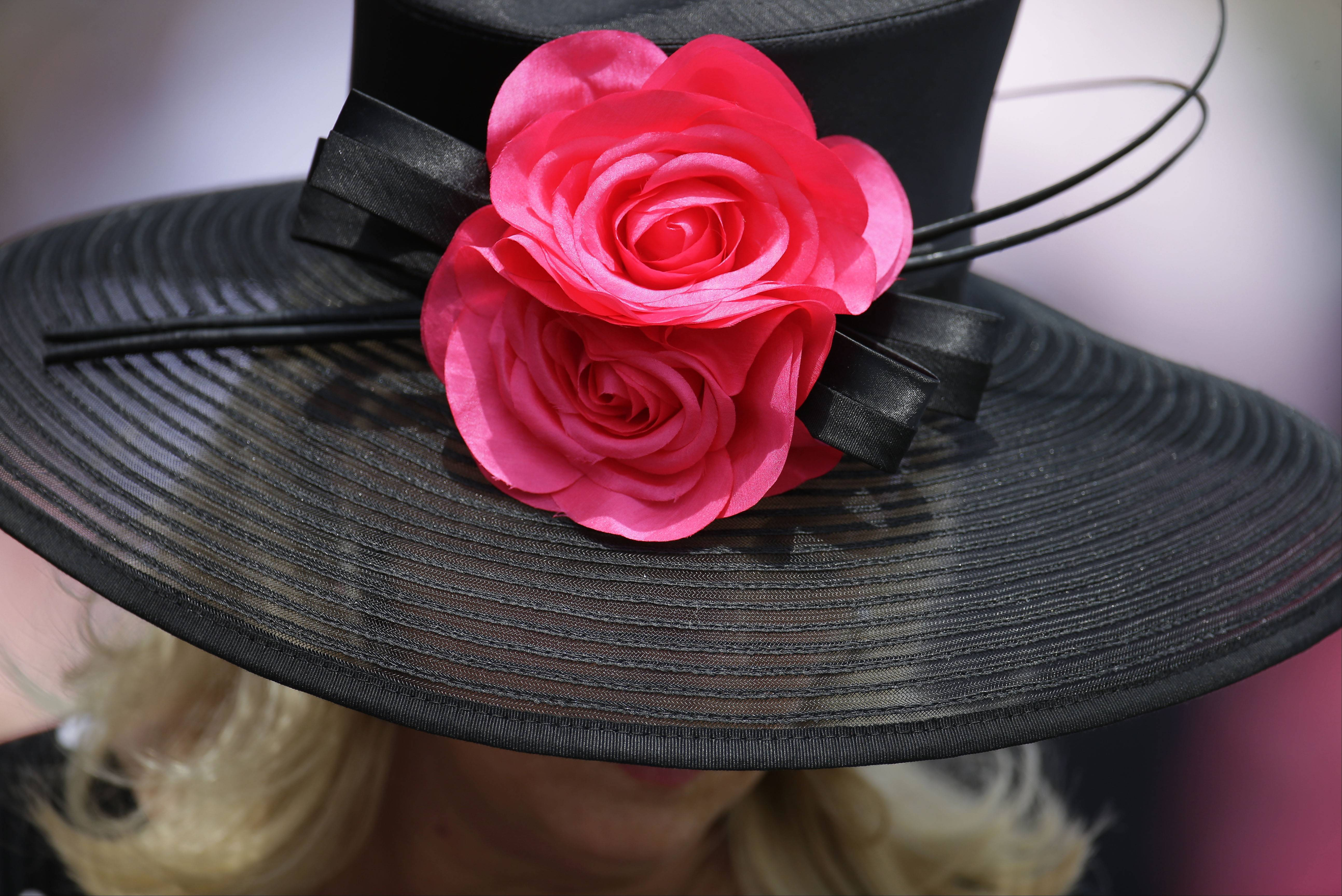 A woman looks over a racing program before the 140th running of the Kentucky Derby horse race at Churchill Downs Saturday in Louisville, Ky.
