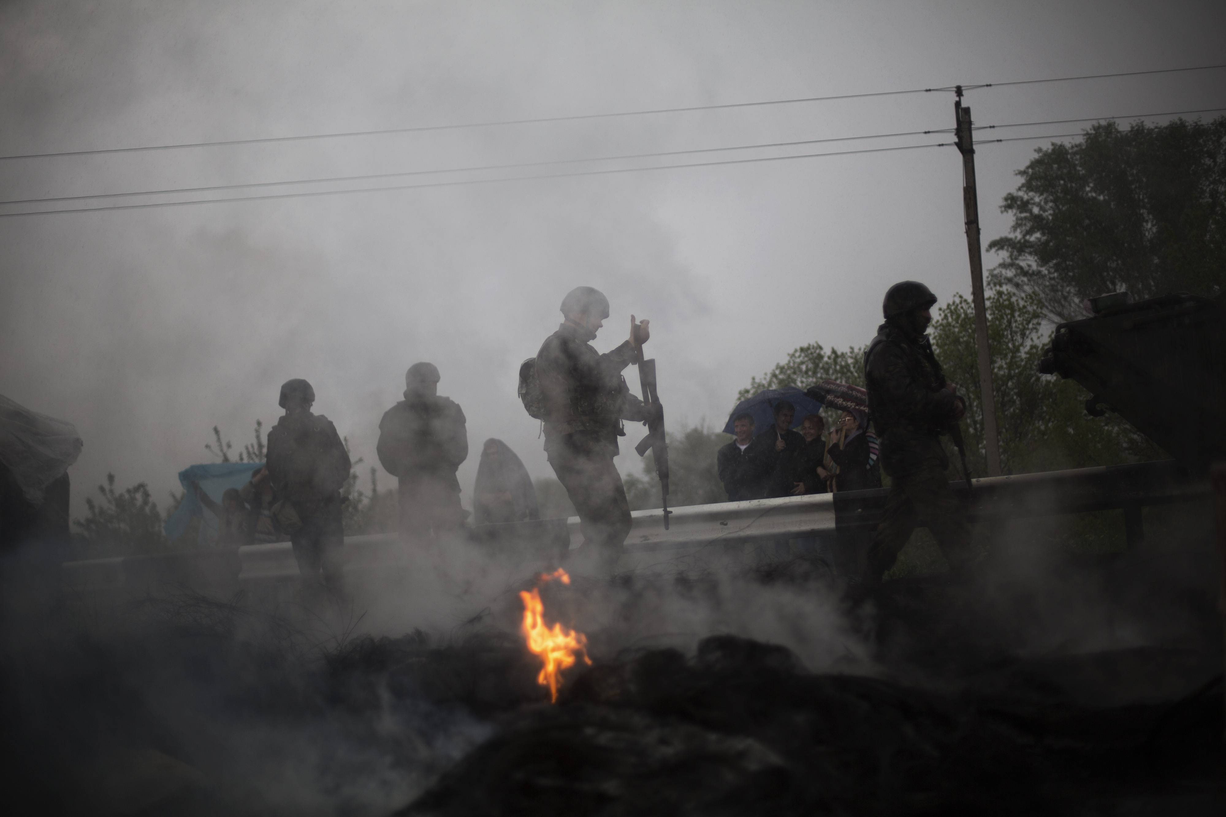 A Ukrainian Army soldier walks behind a burnt barricade Friday while Pro Russia civilians block the road to Slaviansk in the village of Andreevka, Ukraine. Russia has massed tens of thousands of troops in areas near Ukraine's border.