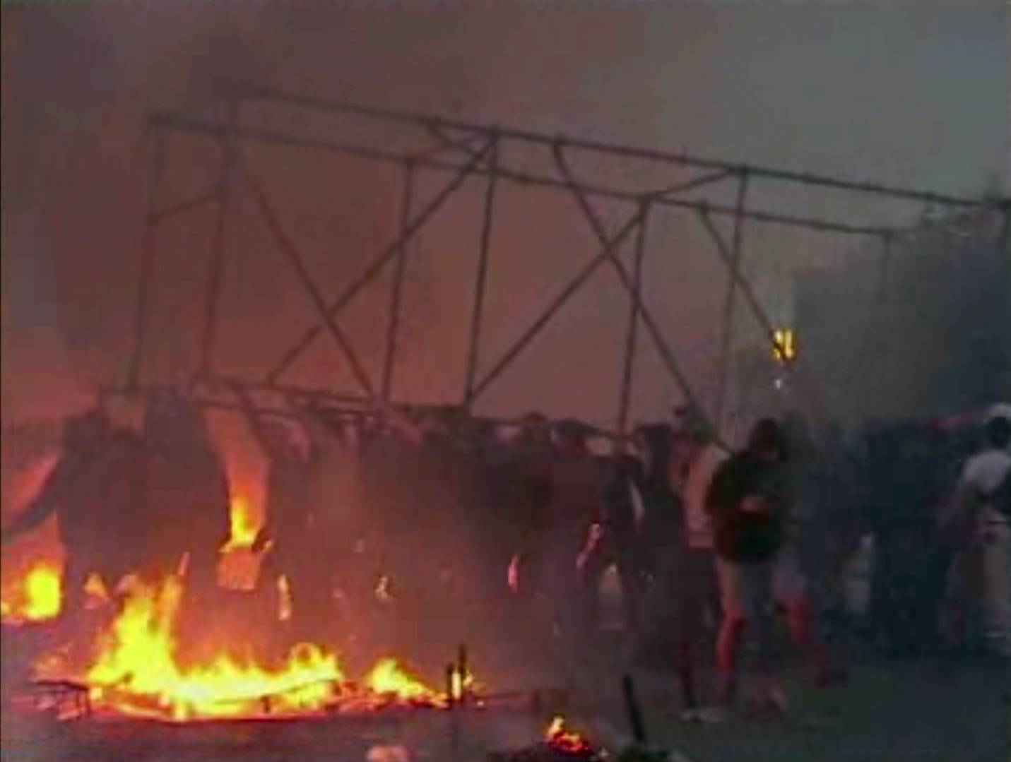 This image made from AP video shows people carrying a scaffolding frame through fires on the ground in Odessa, Ukraine, on Friday, May 2, 2014. Deadly clashes took place in the southern Ukraine port of Odessa on Friday, triggered by Ukraine's offensive to recapture the eastern city of Slovyansk from pro-Russia forces.