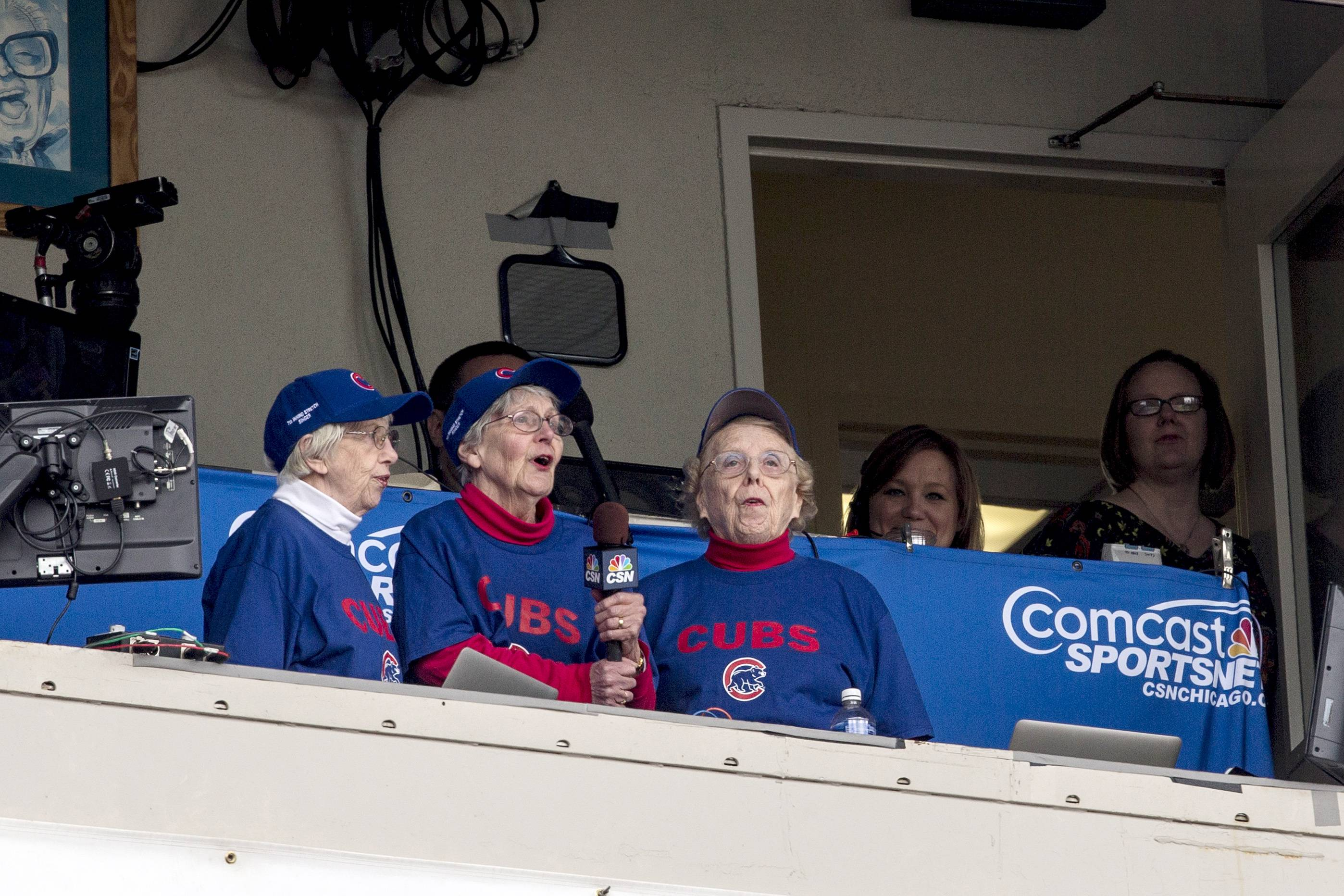 "From left, Mary Manning, Margaret Manning, and Barbara Ernesti, all relatives of Margaret ""Midge"" Donahue, sing during the seventh inning stretch during a baseball game between the Chicago Cubs and the St. Louis Cardinals on Saturday, May 3, 2014, in Chicago. The Cubs won 3-0. Donahue was hired by the Cubs as a stenographer in 1919, and rose to be the vice president of the team. (AP Photo/Andrew A. Nelles)"