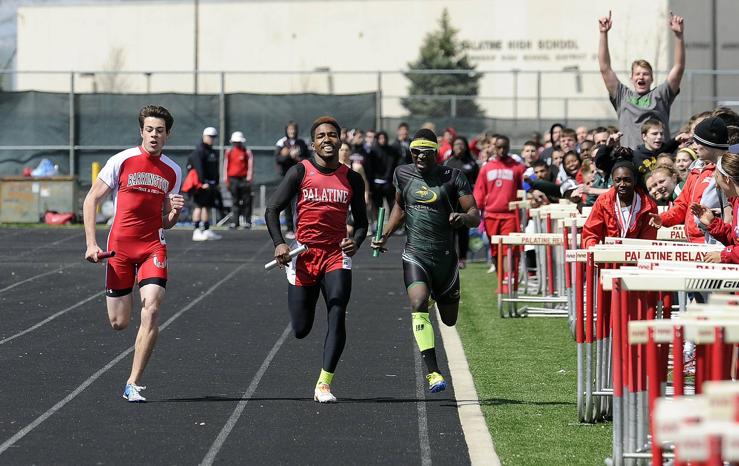 Fremd's Jawan Gaines, right, edges out Barrington and Palatine down the stretch in the 1,600-meter relay on Saturday in the Palatine Relays at Chic Anderson Field.