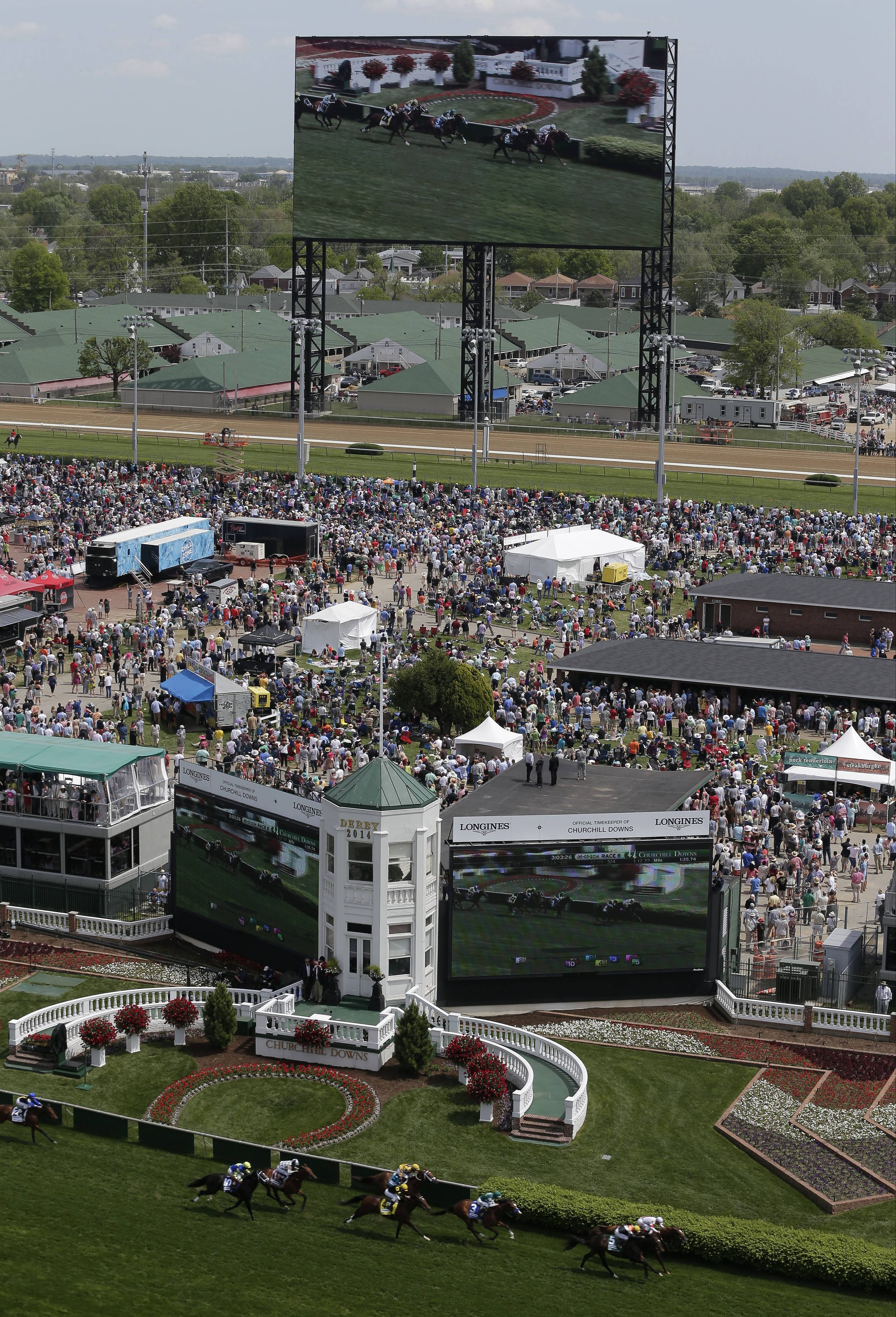 Fans watch a race on a large video screen Saturday before the 140th running of the Kentucky Derby horse race at Churchill Downs.