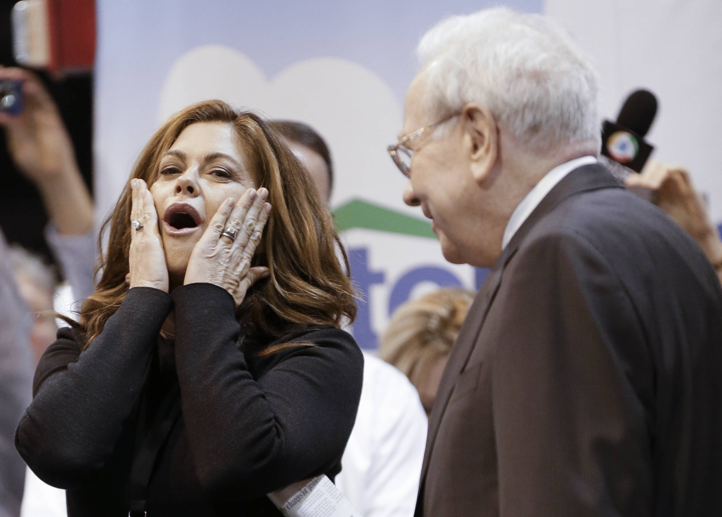 Berkshire Hathaway Chairman and CEO Warren Buffett, right, watches former super model and current business woman Kathy Ireland react Saturday after making a bad throw in the newspaper throwing competition prior to the annual shareholders meeting.