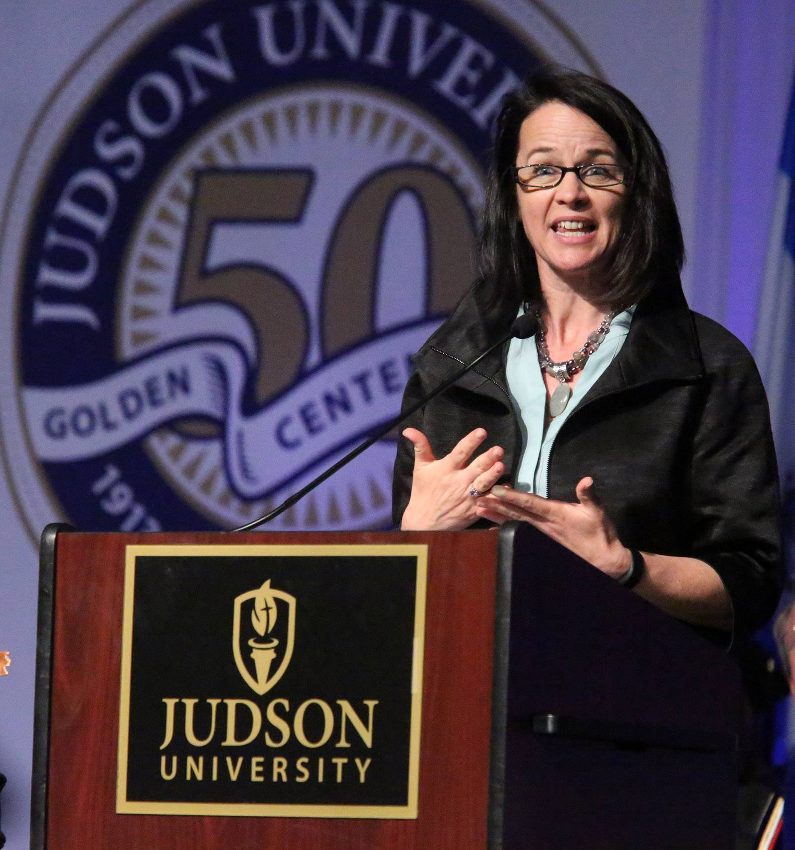 Author Mindy Caliguire delivers the keynote address to graduates at Judson University's golden centennial commencement on Saturday in Elgin.
