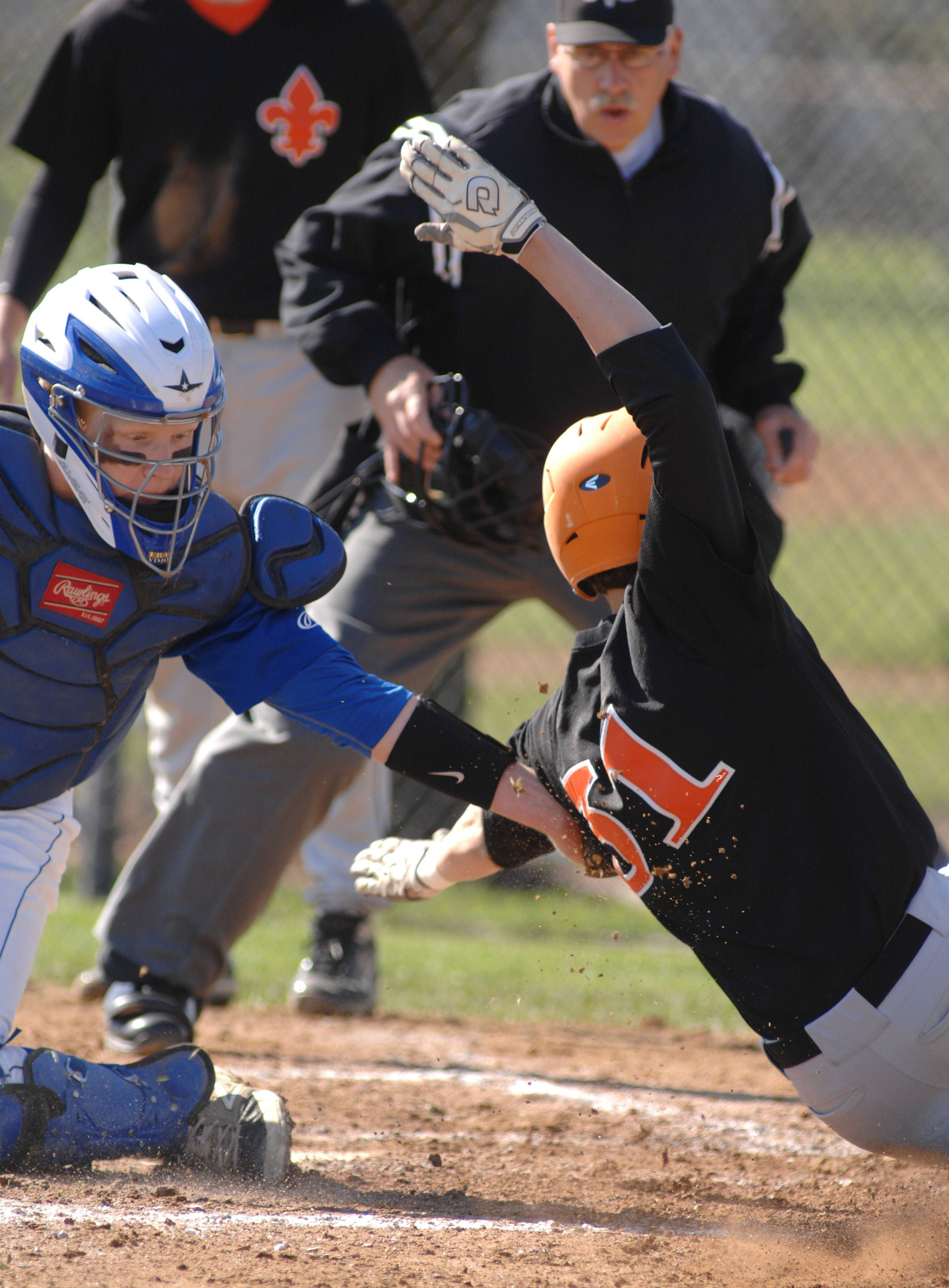Geneva catcher Nathan Montgomery tags St. Charles East's Mike Settle in the second inning on Saturday, May 3. Originally counted as a run by umpires, it was later retracted as it was determined Settle never touched home plate.