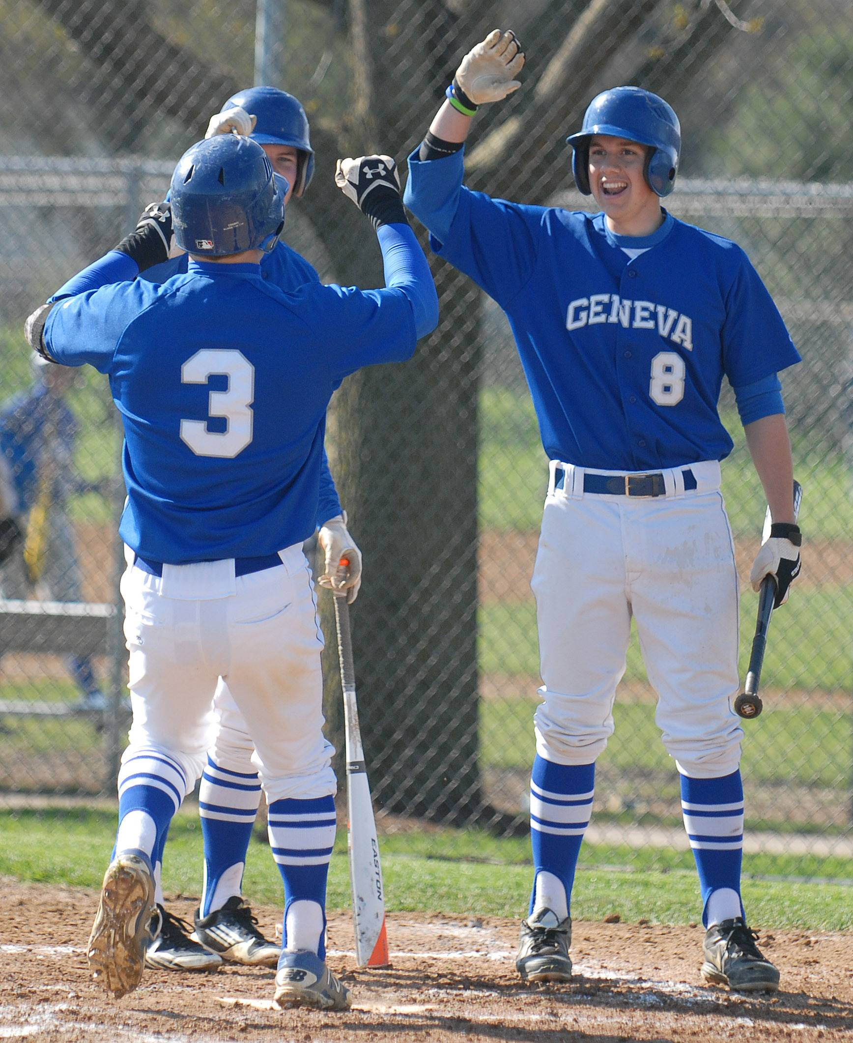 Geneva's Nick Derr (3) is welcomed at home plate by teammates Jason Croci, left, and Ben Chally, right, after hitting a home run in the first inning vs. St. Charles East on Saturday, May 3.