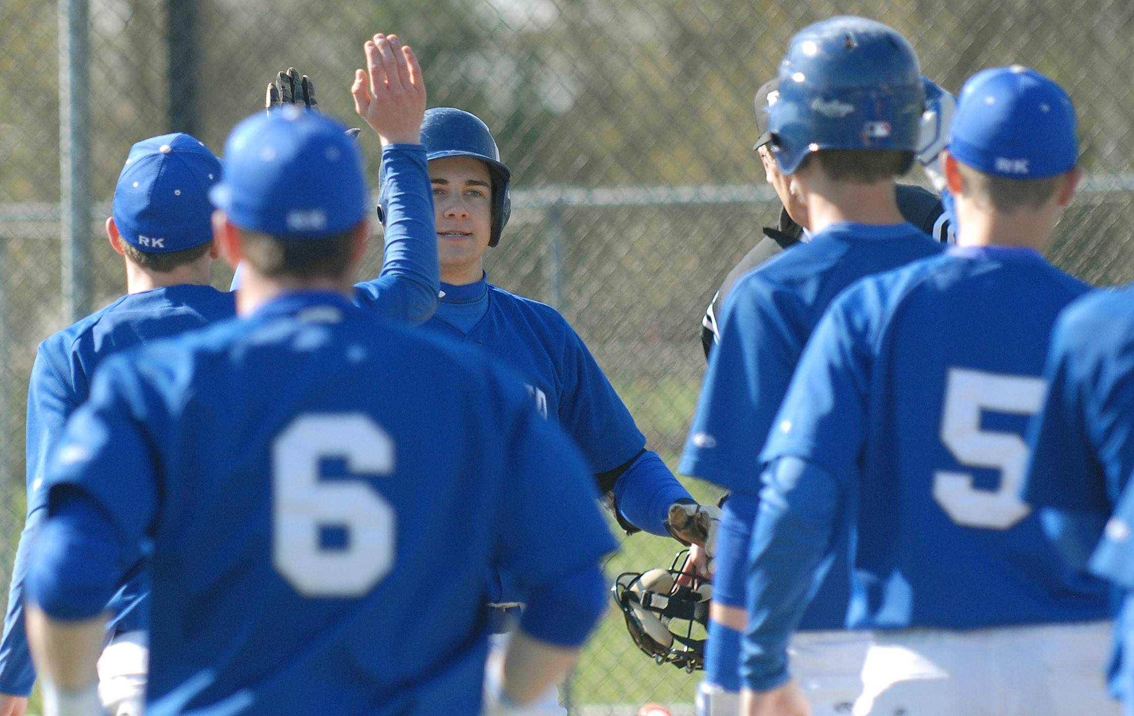 Geneva's Nick Derr (center, facing) is congratulated by teammates after scoring a home run in the first inning vs. St. Charles East on Saturday, May 3.