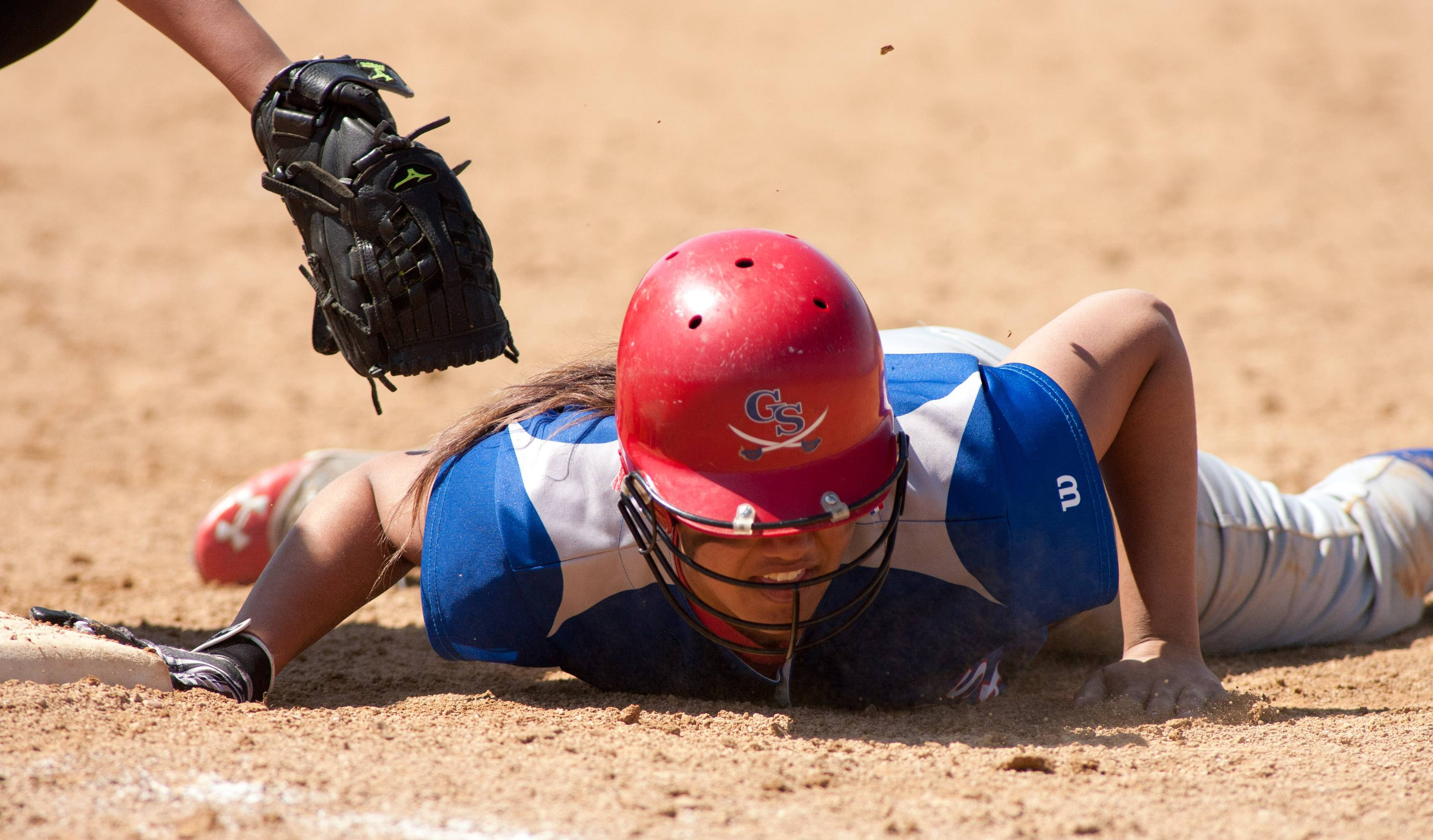 Glenbard South's Ashton Cattenhead slides safely back into first base against Morton during girls softball action in Lombard.
