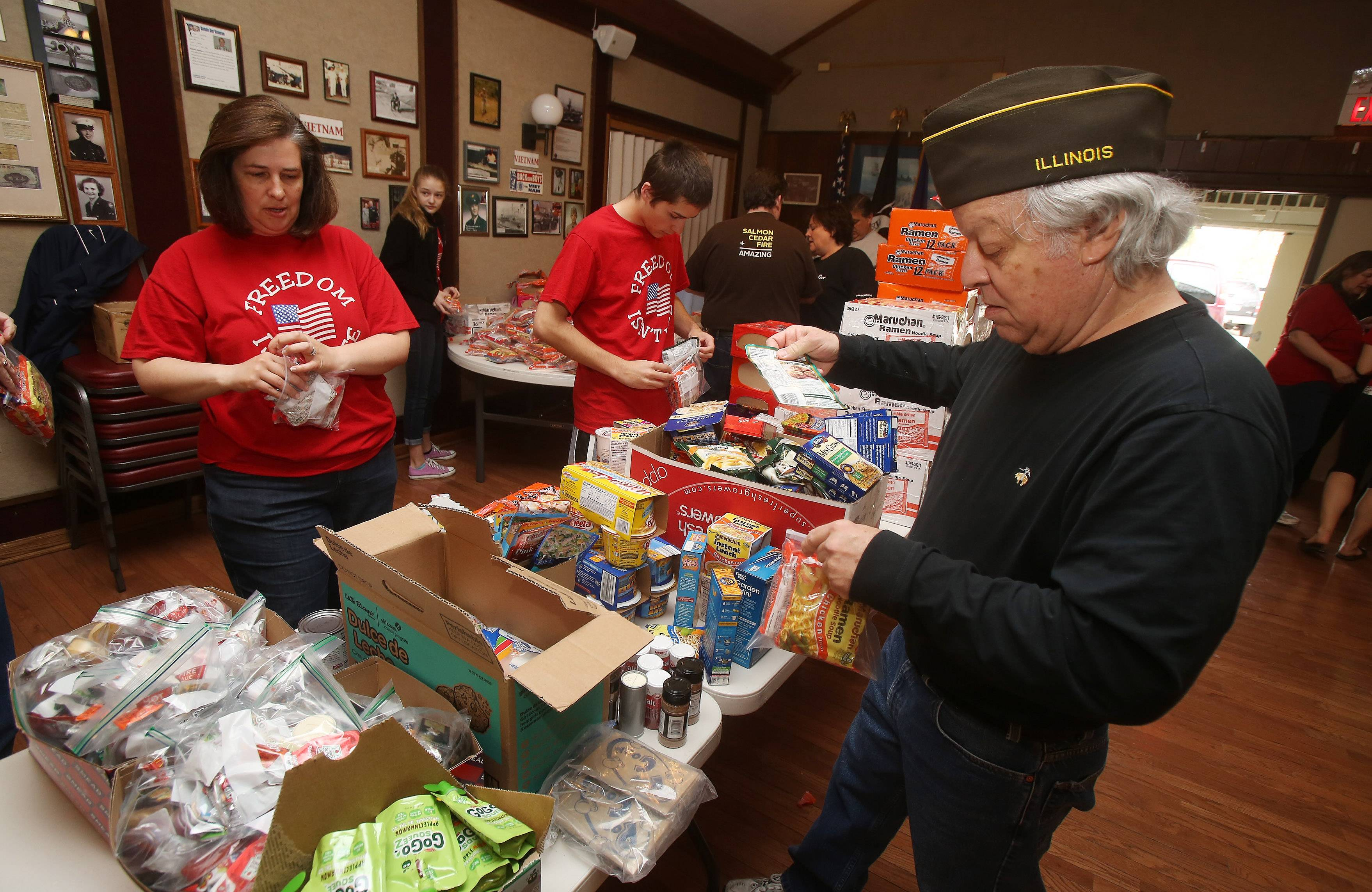 Marybeth Buck of Arlington Heights, left, and her son Matthew, 16, with Roger Santagato of VFW Post 981 join family and friends of fallen Arlington Heights Marine James Stack packing boxes of donations at the Arlington Heights American Legion Hall. The donations will be sent to troops serving overseas.