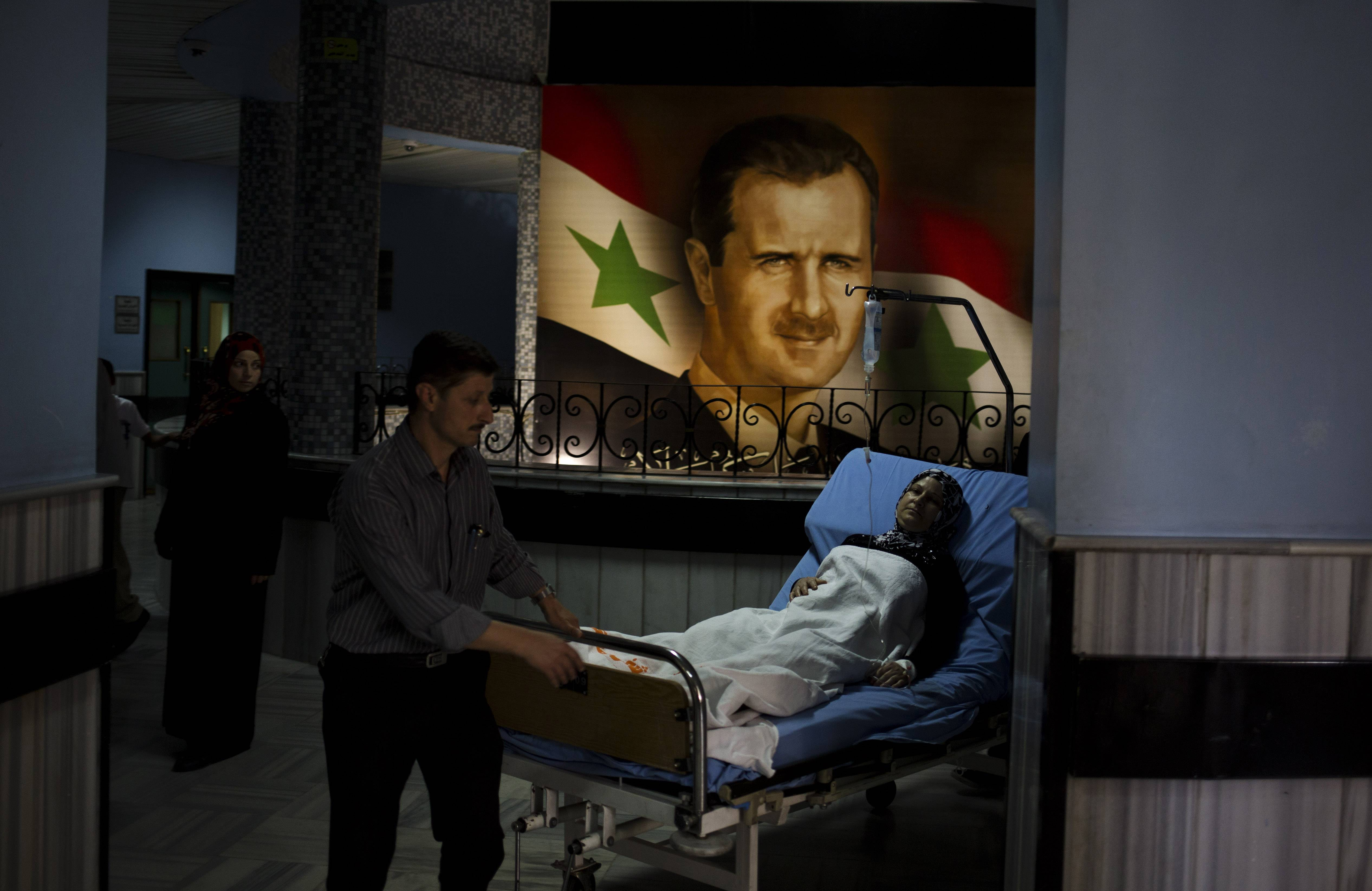 A patient is wheeled through the Damascus General Hospital past a portrait of the President Bashar Assad in Damascus, Syria, Sunday. An official with Syria's Supreme constitutional Court said Assad and two others will be candidates in coming June presidential elections.