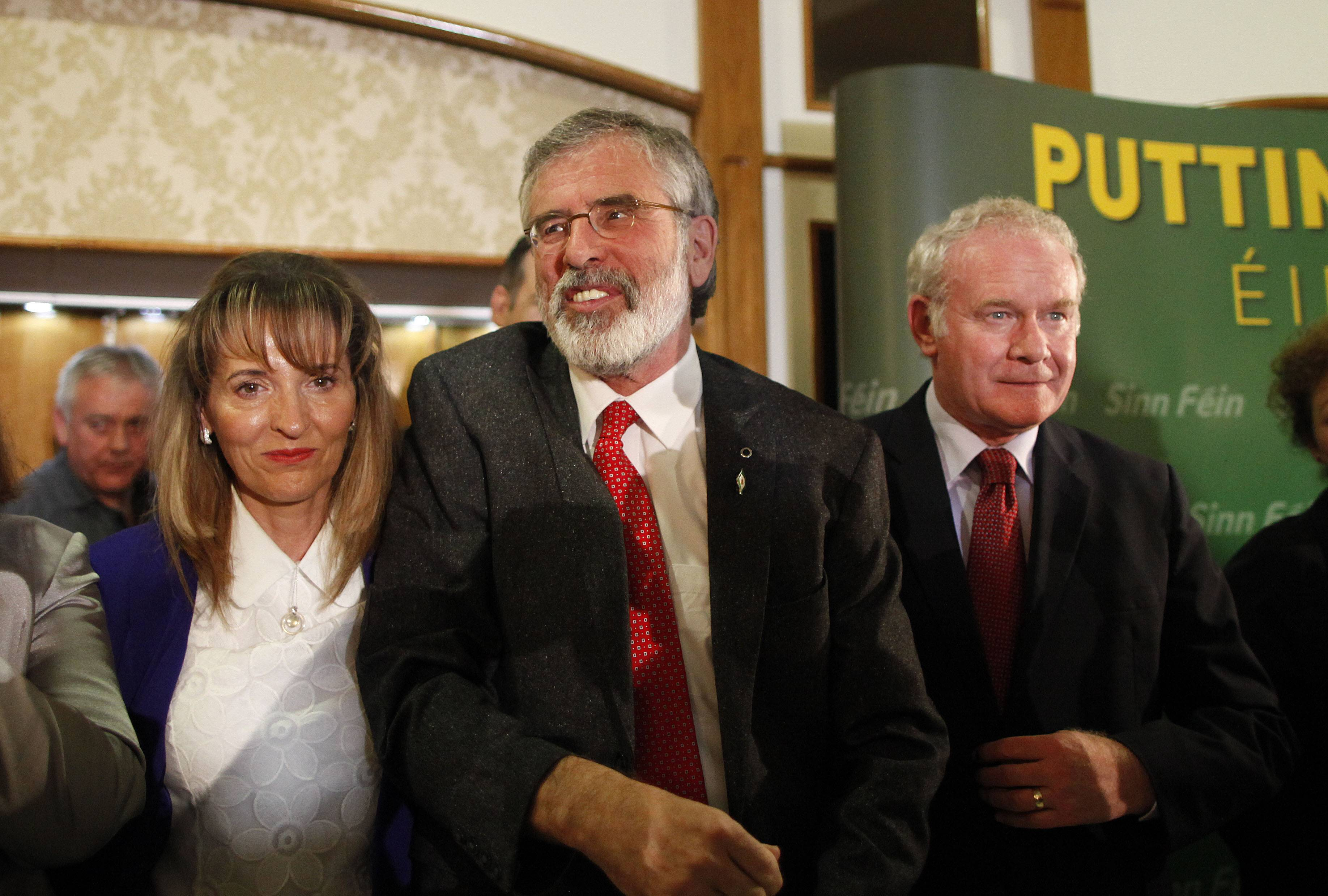 Sinn Fein President Gerry Adams, center, Martina Anderson, left, and Martin McGuinness speak to the media in West Belfast, Northern Ireland, Sunday. Adams was released without charge Sunday after five days of police questioning over his alleged involvement in a decades-old Irish Republican Army killing, an event that has driven a dangerous wedge into Northern Ireland's unity government.