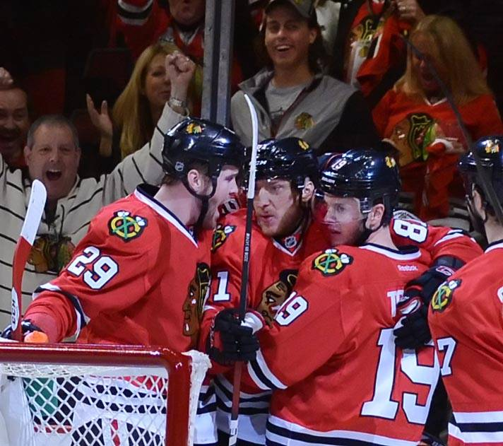 Chicago Blackhawks center Jonathan Toews, right, is hugged by teammate Marion Hossa as Brian Bickell comes to celebrate Toews first-period goal Sunday in Game 2 of the second round of the Stanley Cup Playoffs at the United Center in Chicago.