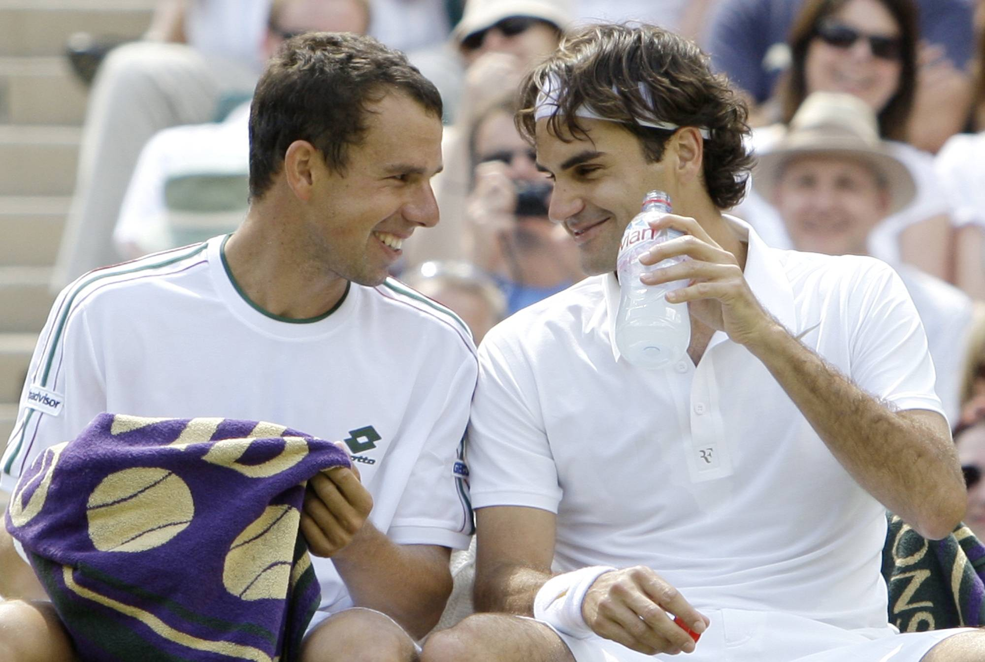 Federer shares a joke with Slovakia's Dominik Hrbaty, as they sit alongside each other, during their Men's Singles, first round match on the Centre Court at Wimbledon, Monday, June 23, 2008.