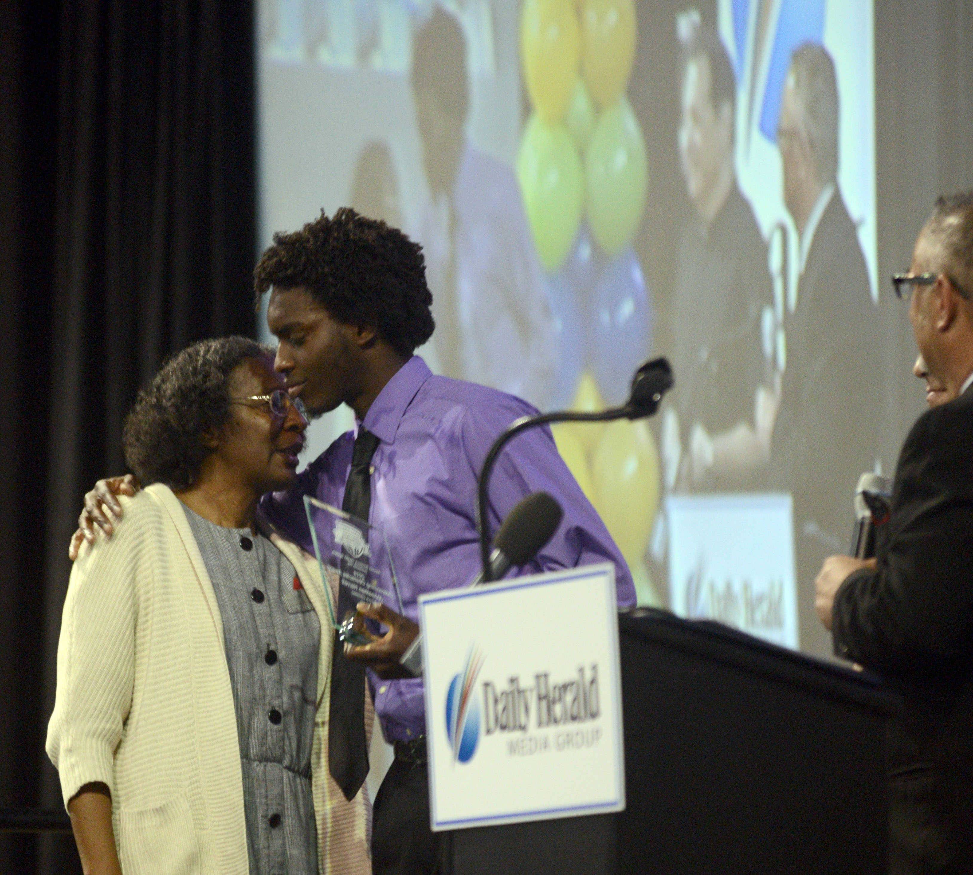 Aurora Christian High School basketball player Johnathan Harrell hugs his mother Sunday after receiving an Overcoming Obstacle Award during the Daily Herald Prep Sports Excellence banquet at the Sears Centre Arena in Hoffman Estates. Johnathan's mother encouraged him to play in a game last winter just a day after his brother was killed in a car accident.