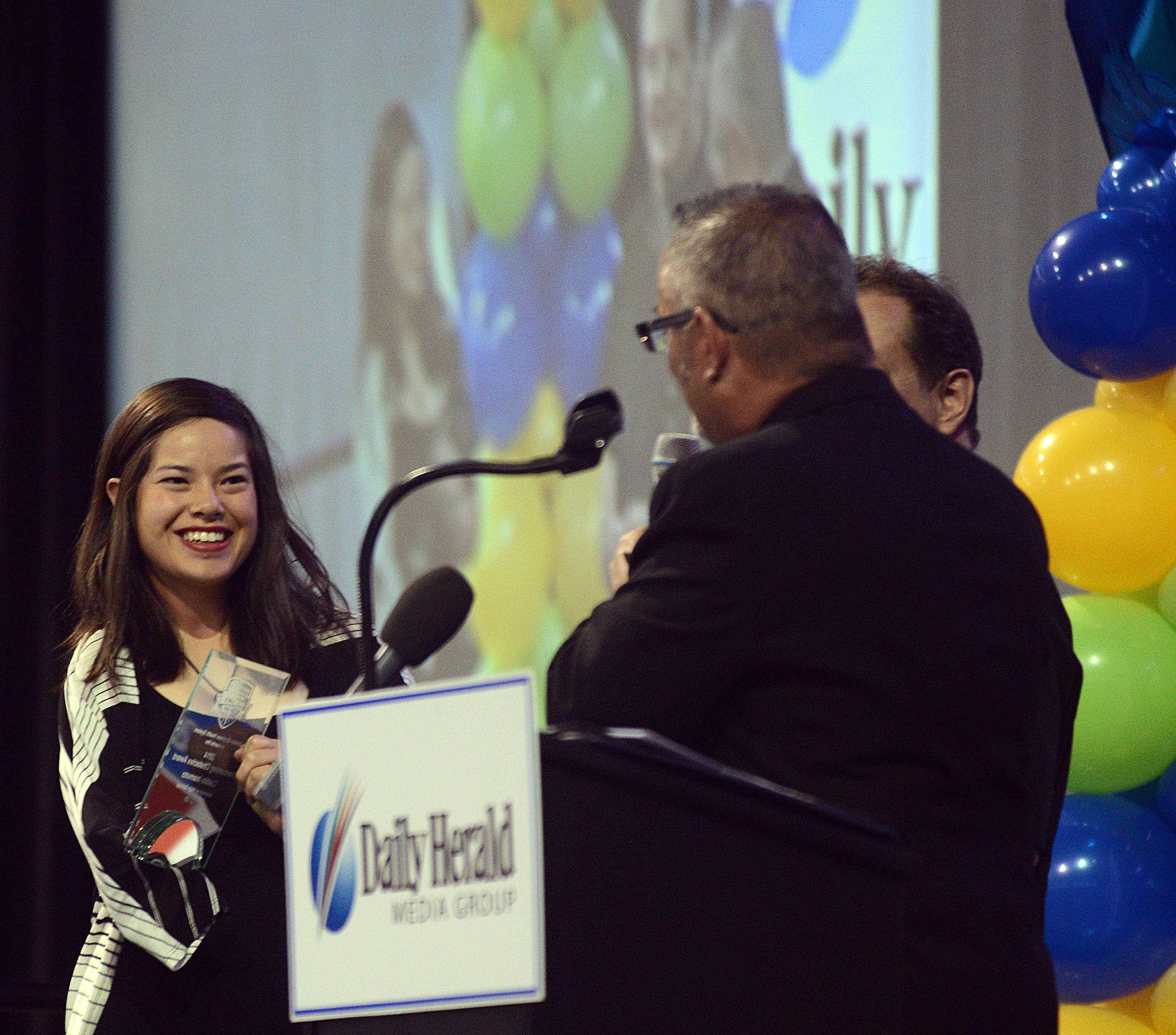 Caitlin Inamoto of Barrington High School, left, receives an Overcoming Obstacles Award during the Daily Herald Prep Sports Excellence banquet at the Sears Centre Arena in Hoffman Estates. Inamoto, who was born with the full use of just one of her arms, excels in softball.