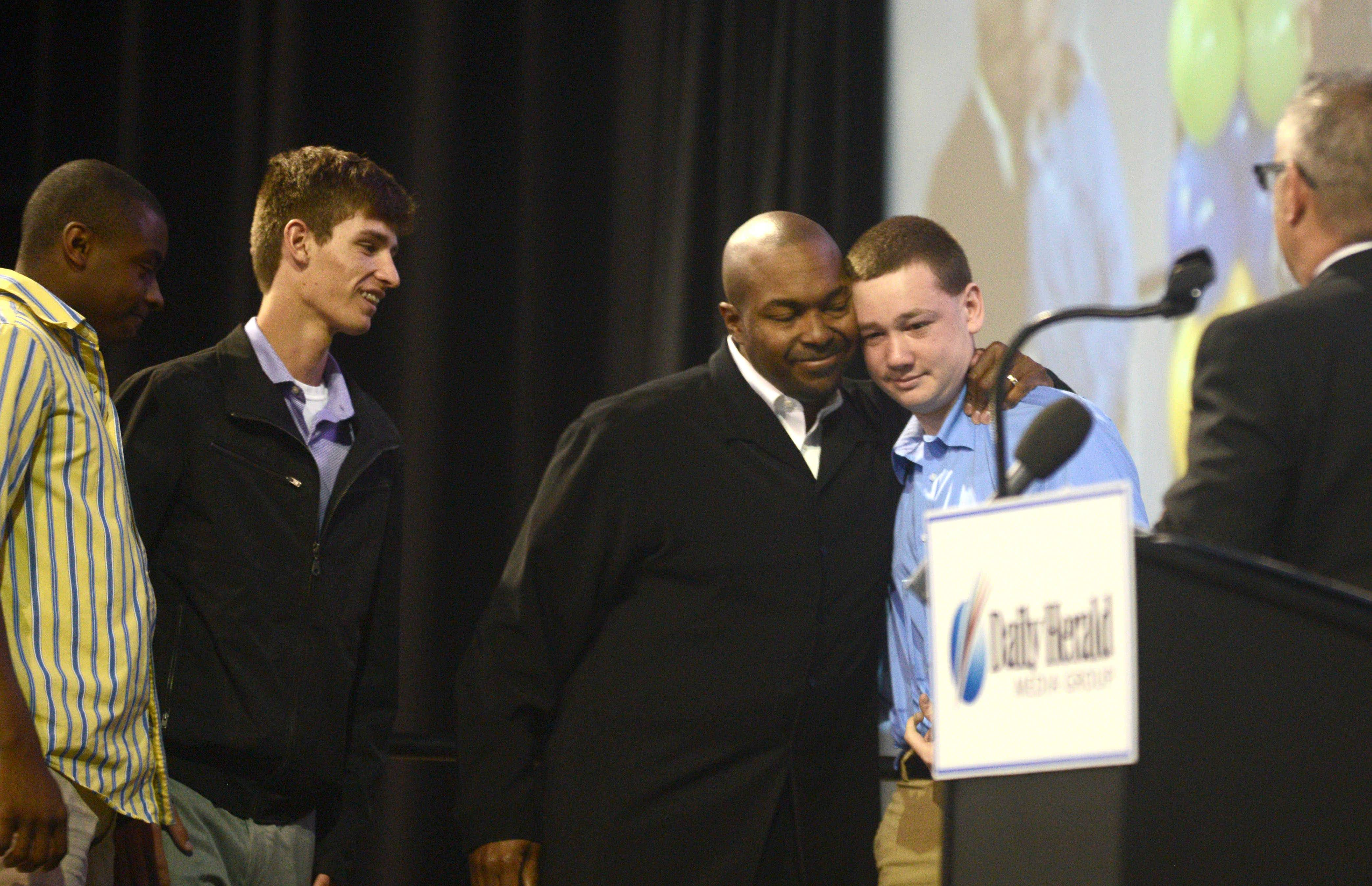 Members of the Westminster Christian High School football team receive a Spirit of Sportsmanship Award during the Daily Herald Prep Sports Excellence banquet at the Sears Centre Arena in Hoffman Estates. Team members rallied around the ill father of quarterback Max Tucker, right, to win the first game in program history.
