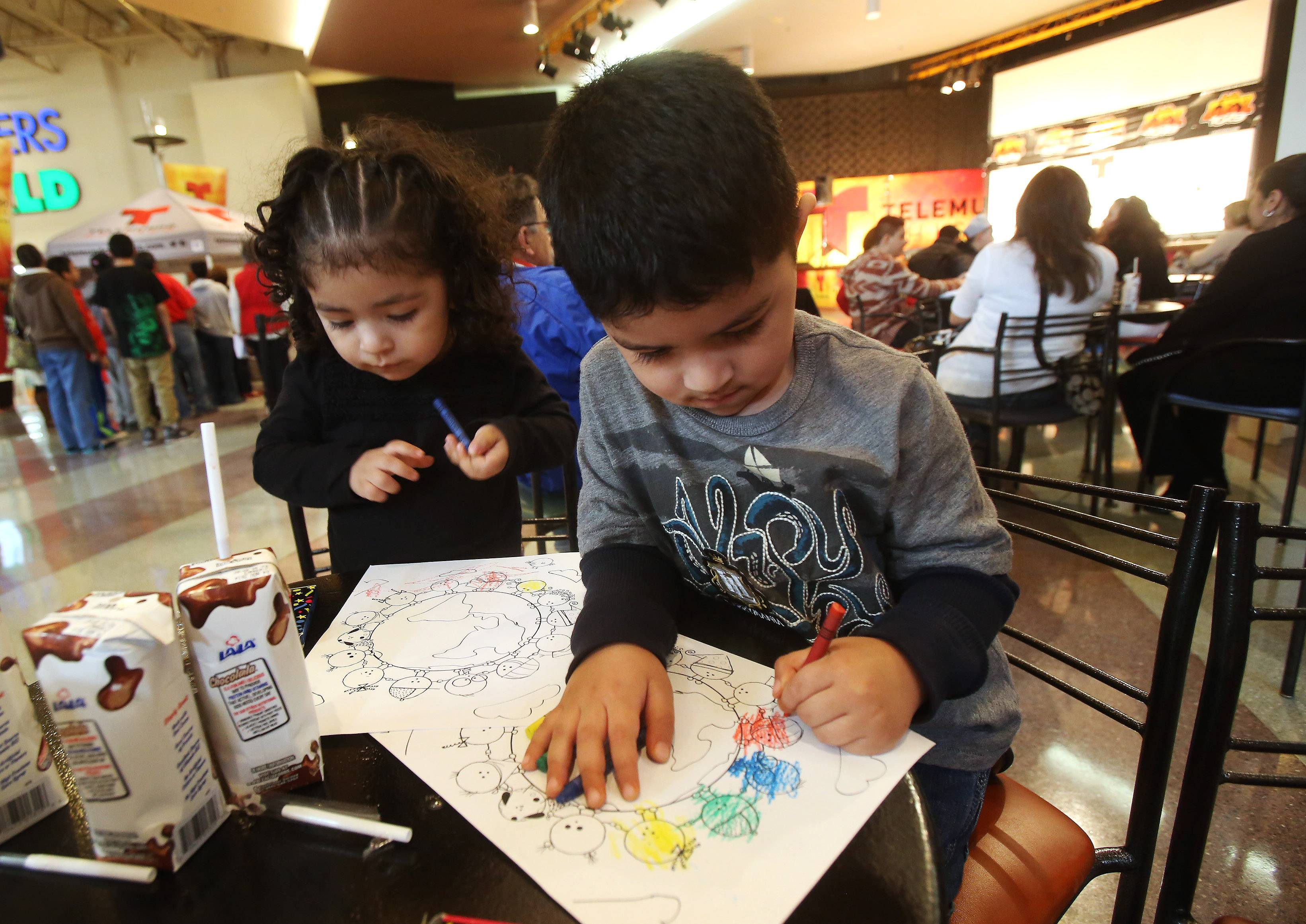 Alexa Tello, 3, and her brother, Bryan, 4, of Waukegan color during the first Cinco de Mayo celebration at Gurnee Mills on Sunday. The event include several Latino artists, food samplings, face paintings and giveaways.