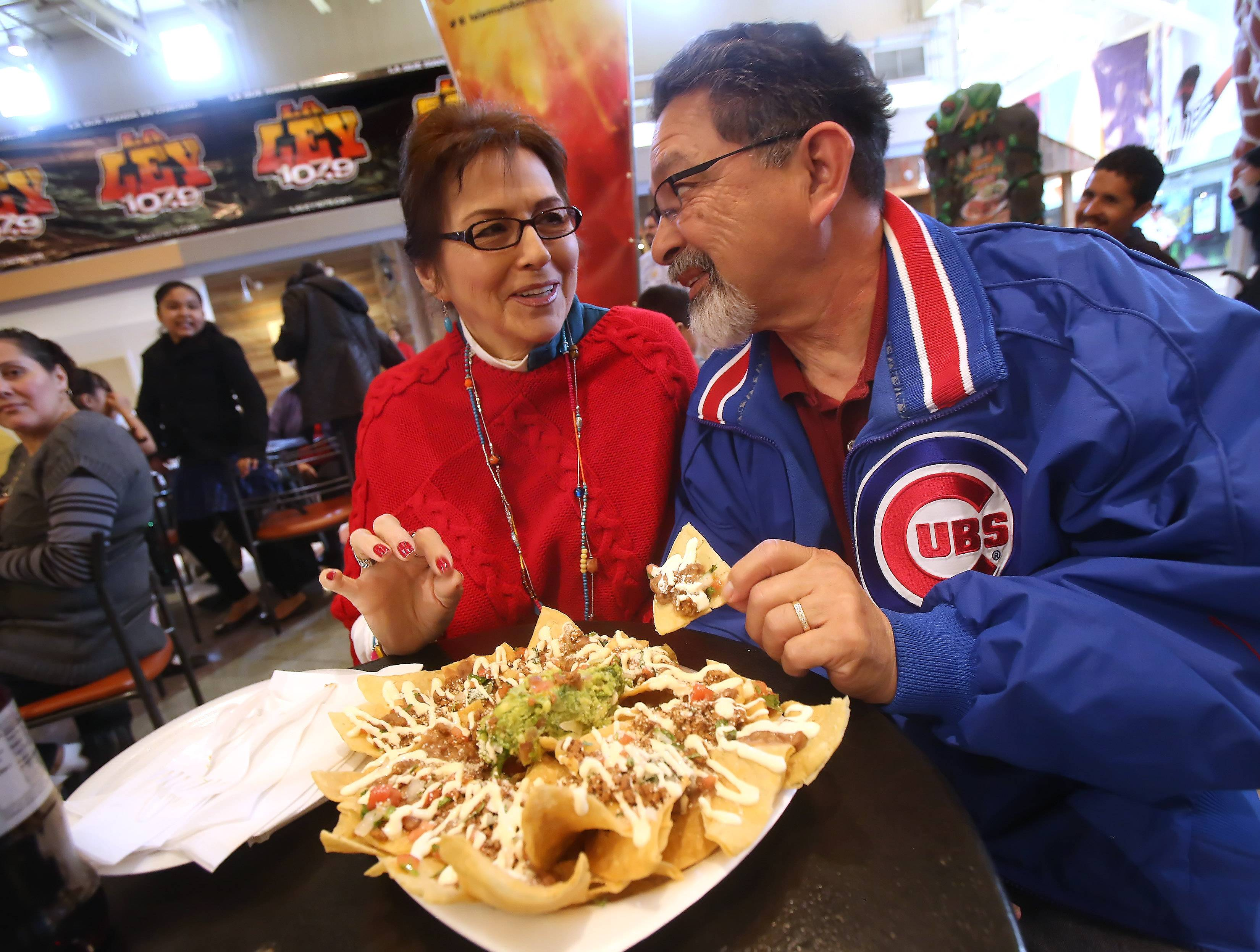 Rosie and Joe Cuellar of Lake Zurich enjoy nachos during the first Cinco de Mayo celebration at Gurnee Mills on Sunday. The event include several Latino artists, food samplings, face paintings and giveaways.