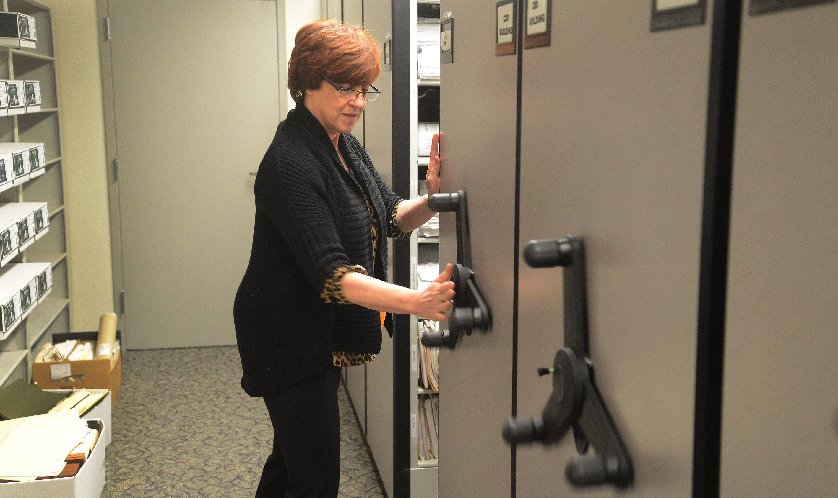 Jane Lentino, Schaumburg permit control clerk, tracks down information for a FOIA request in the basement archives.