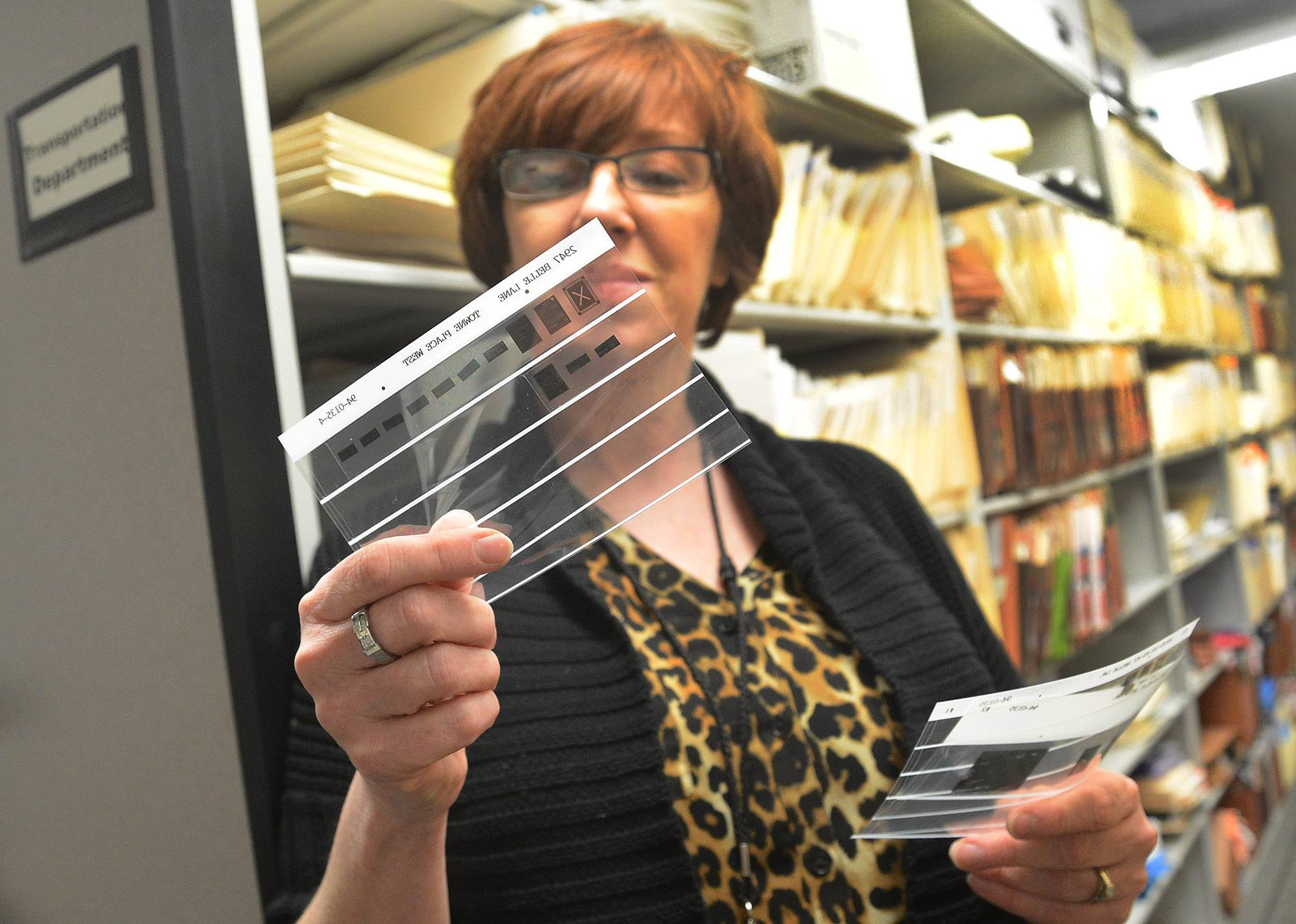 Jane Lentino, Schaumburg permit control clerk, tracks down information for a FOIA request on microfiche.