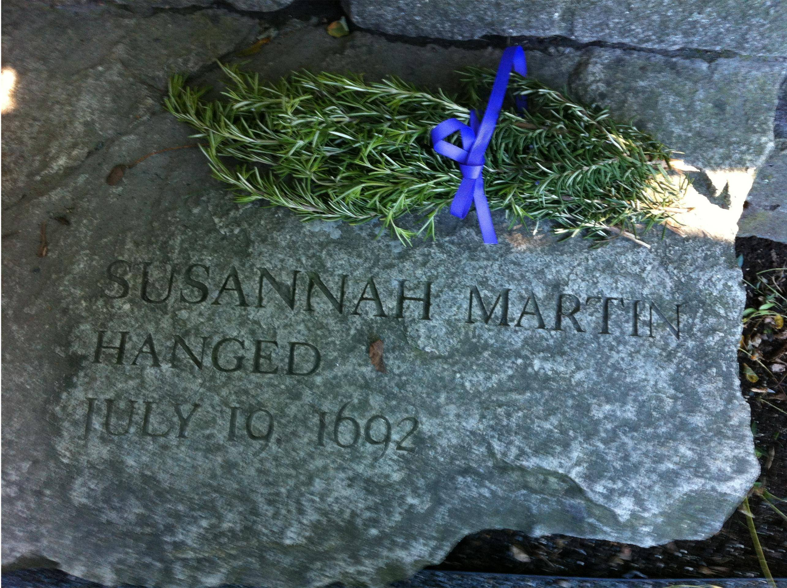 A sprig of rosemary signifying remembrance lies on this bench in Salem, Mass., in memory of Susannah Martin. The woman's great-great-great-great-great-great-great-great-granddaughter Shari Worrell, of Lake Barrington, helped win exoneration and a Christian funeral for Martin and other women executed as witches.