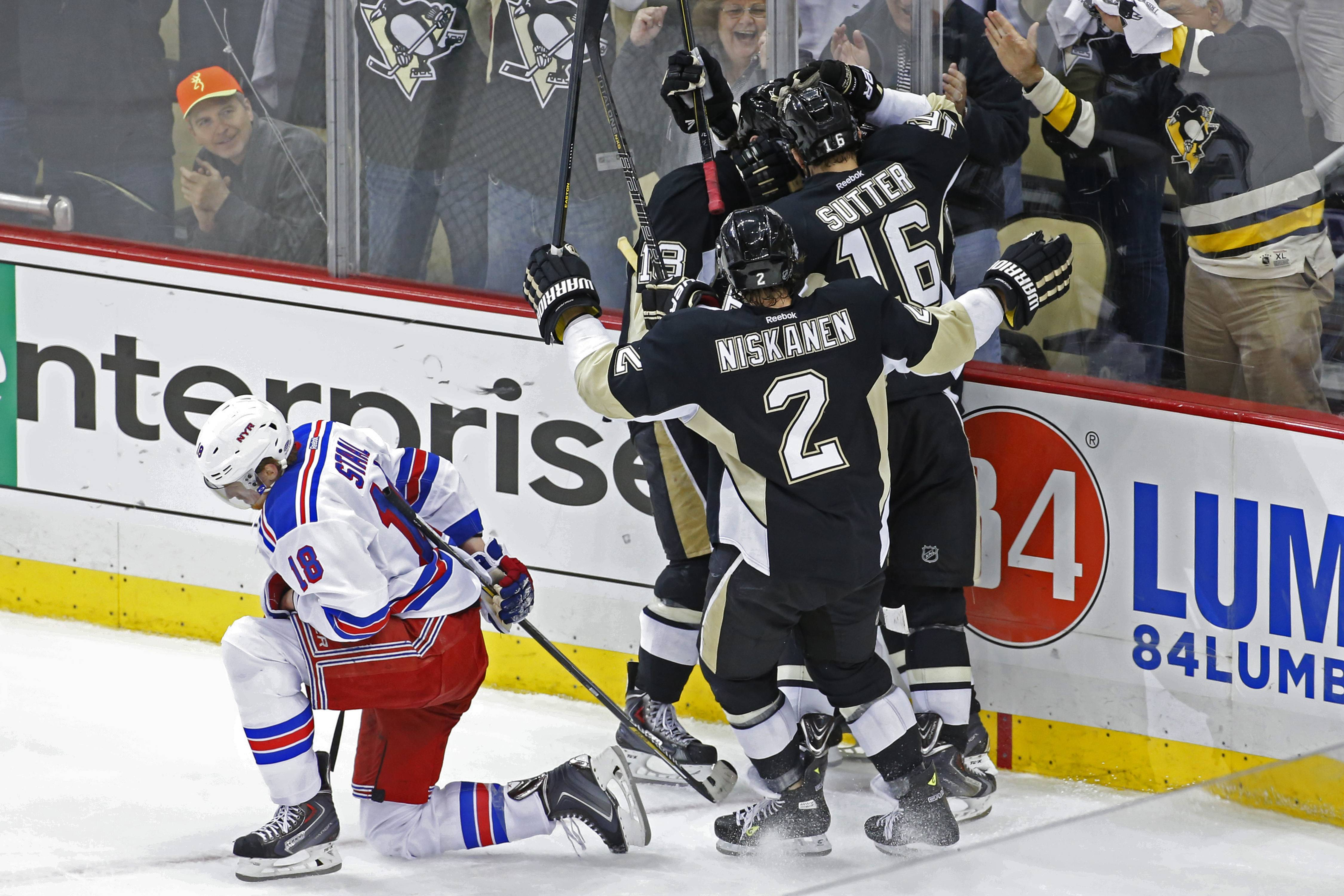 Pittsburgh Penguins' Jussi Jokinen, center not shown, celebrates his goal with teammates as New York Rangers' Marc Staal (18) kneels on the ice in the third period of game 2 of a second-round NHL playoff hockey series against the New York Rangers in Pittsburgh Sunday, May 4, 2014. The Penguins won 3-0, to tie the series at 1-1.