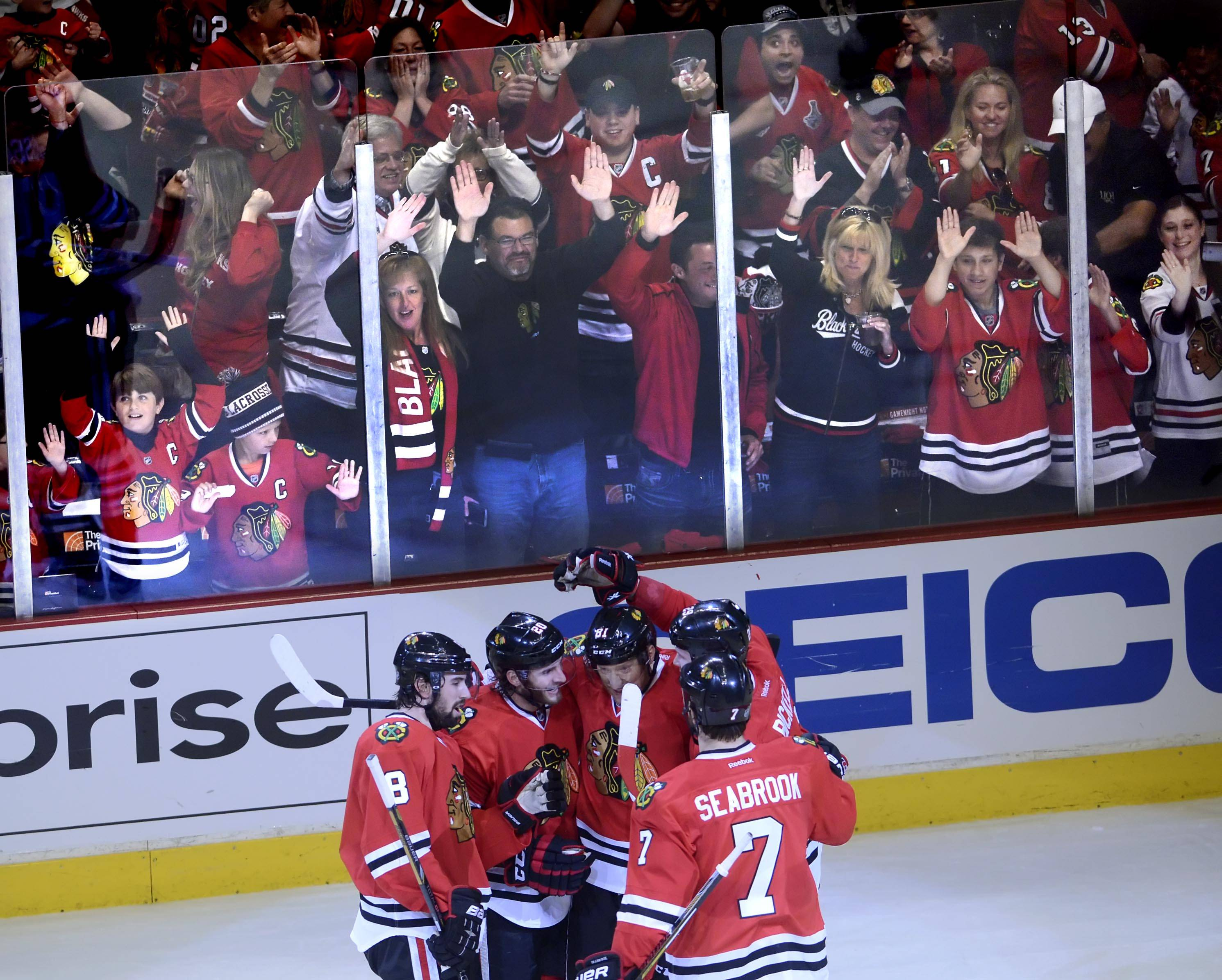 To the delight of the some of the 272nd straight capacity crowd (regular and postseason) at the United Center, the Blackhawks enjoy a group hug after Brandon Saad, second from left, scores in the second period Sunday in Game 2 against the Wild.