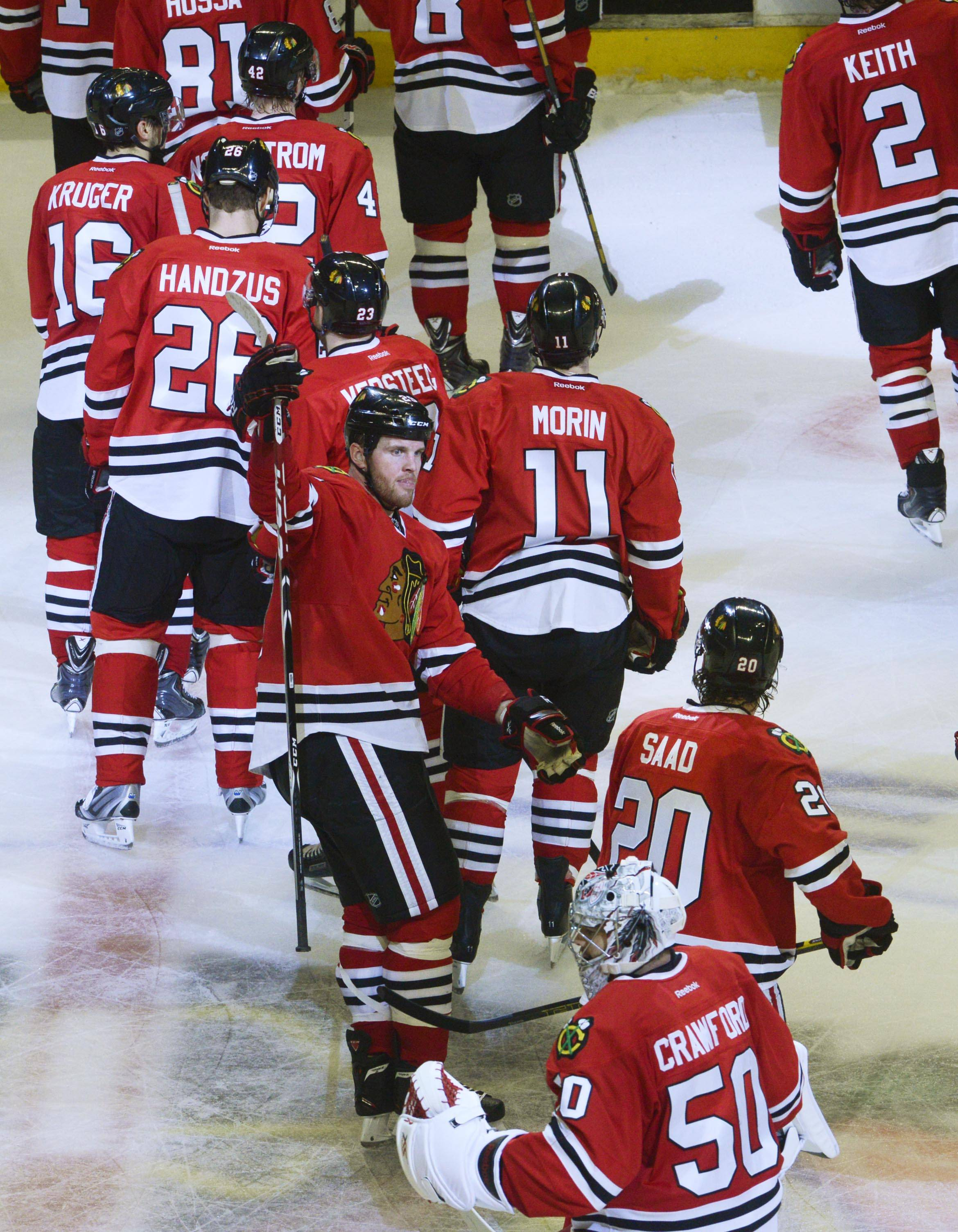 As they leave the ice after a 4-1 victory, Chicago Blackhawks left wing Bryan Bickell comes to congratulate teammate Brandon Saad on a two-goal game against the Minnesota Wild. Bickell also scored a goal.
