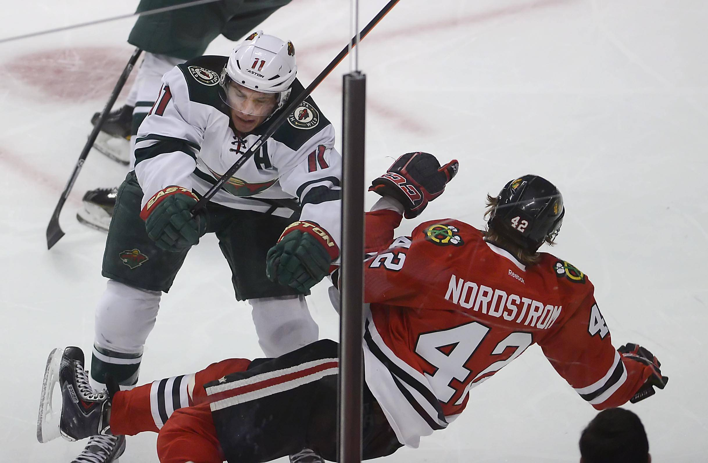 Minnesota Wild left wing Zach Parise checks Chicago Blackhawks center Joakim Nordstrom into the boards.