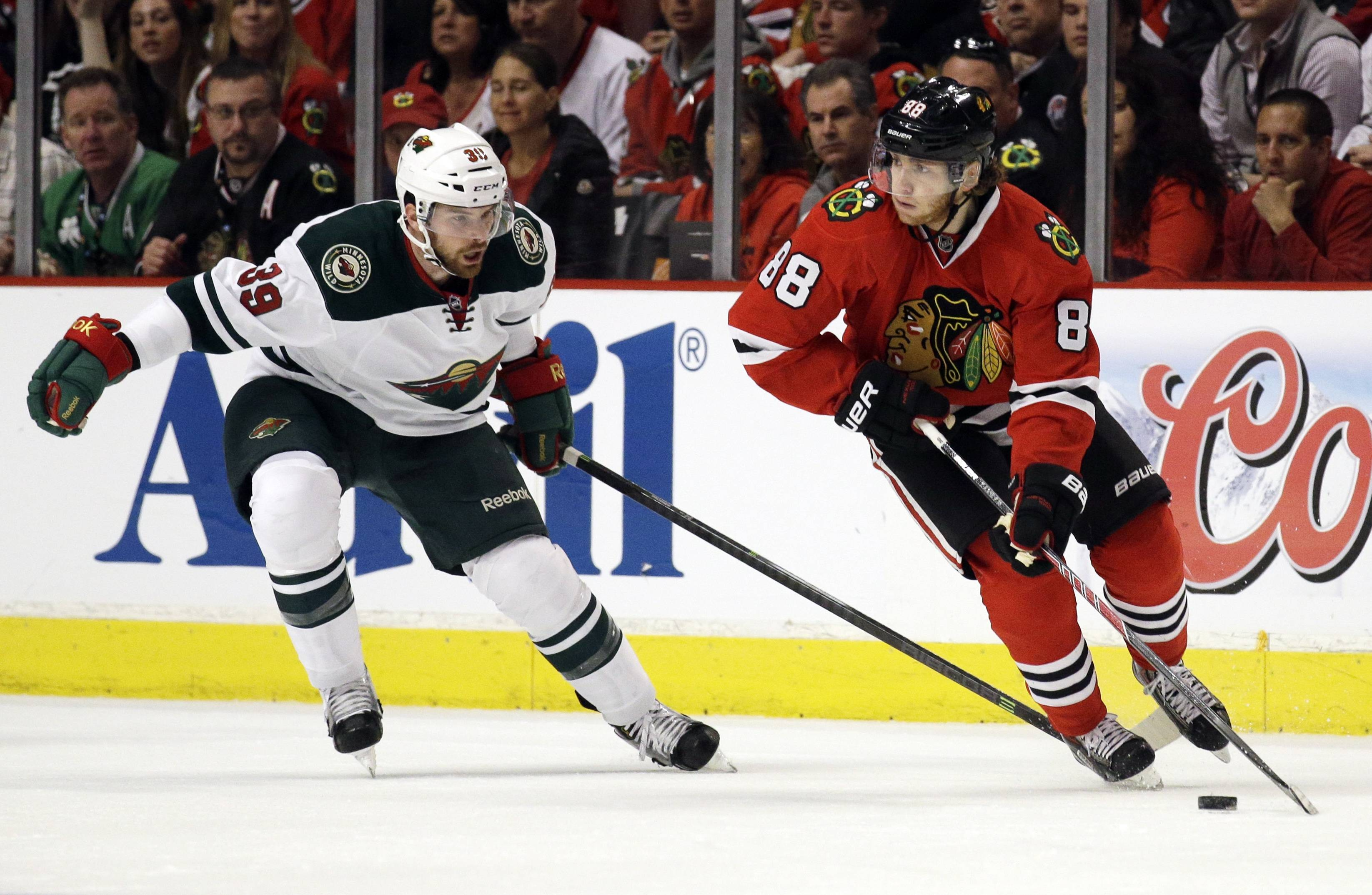 Chicago Blackhawks' Patrick Kane (88), right, controls the puck as he looks to a pass against Minnesota Wild's Nate Prosser (39) during the first period.