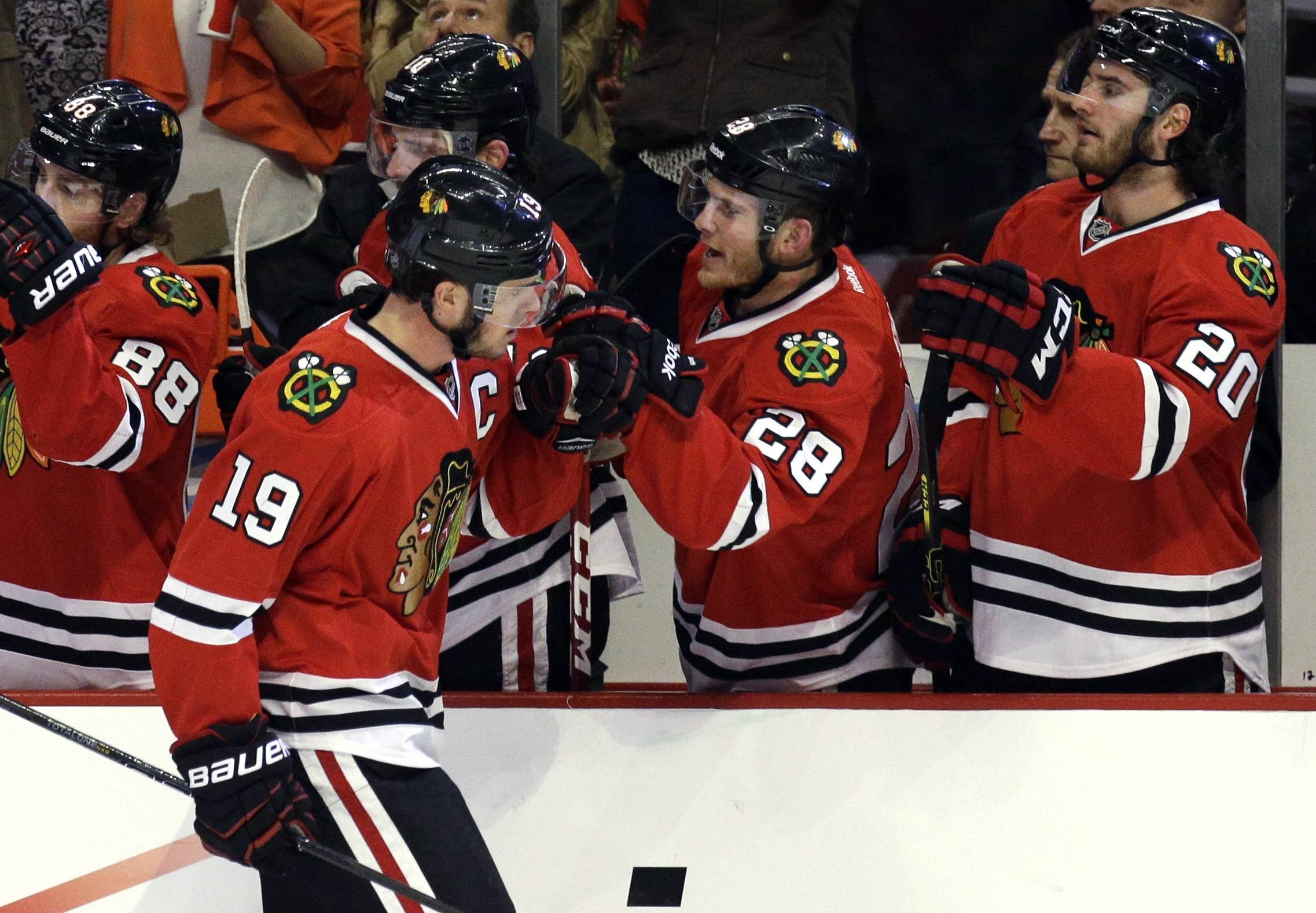 Chicago Blackhawks' Jonathan Toews (19) celebrates with teammates after scoring hi goal during the first period.