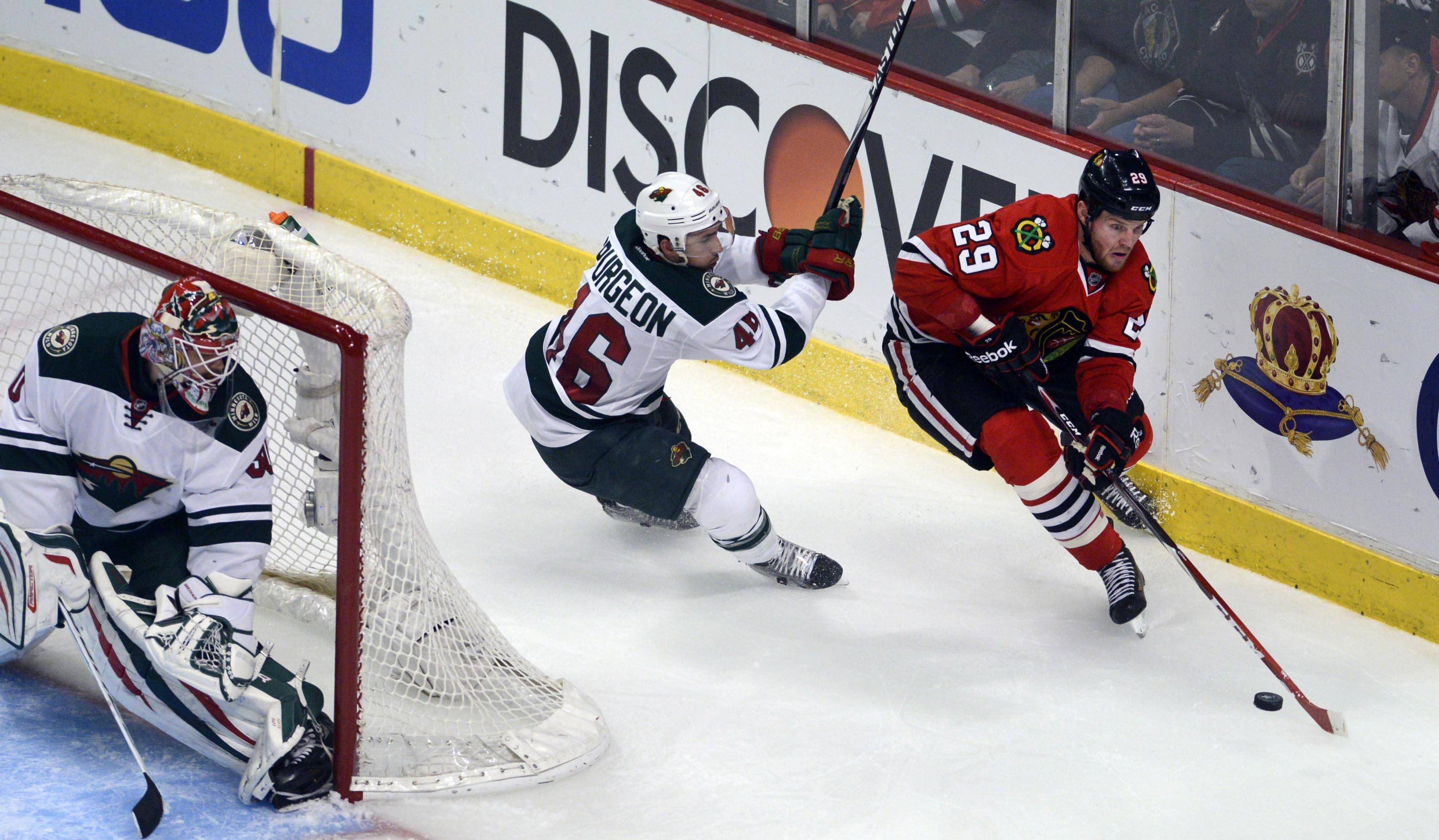 Chicago Blackhawks left wing Bryan Bickell is chased by Minnesota Wild defenseman Jared Spurgeon.