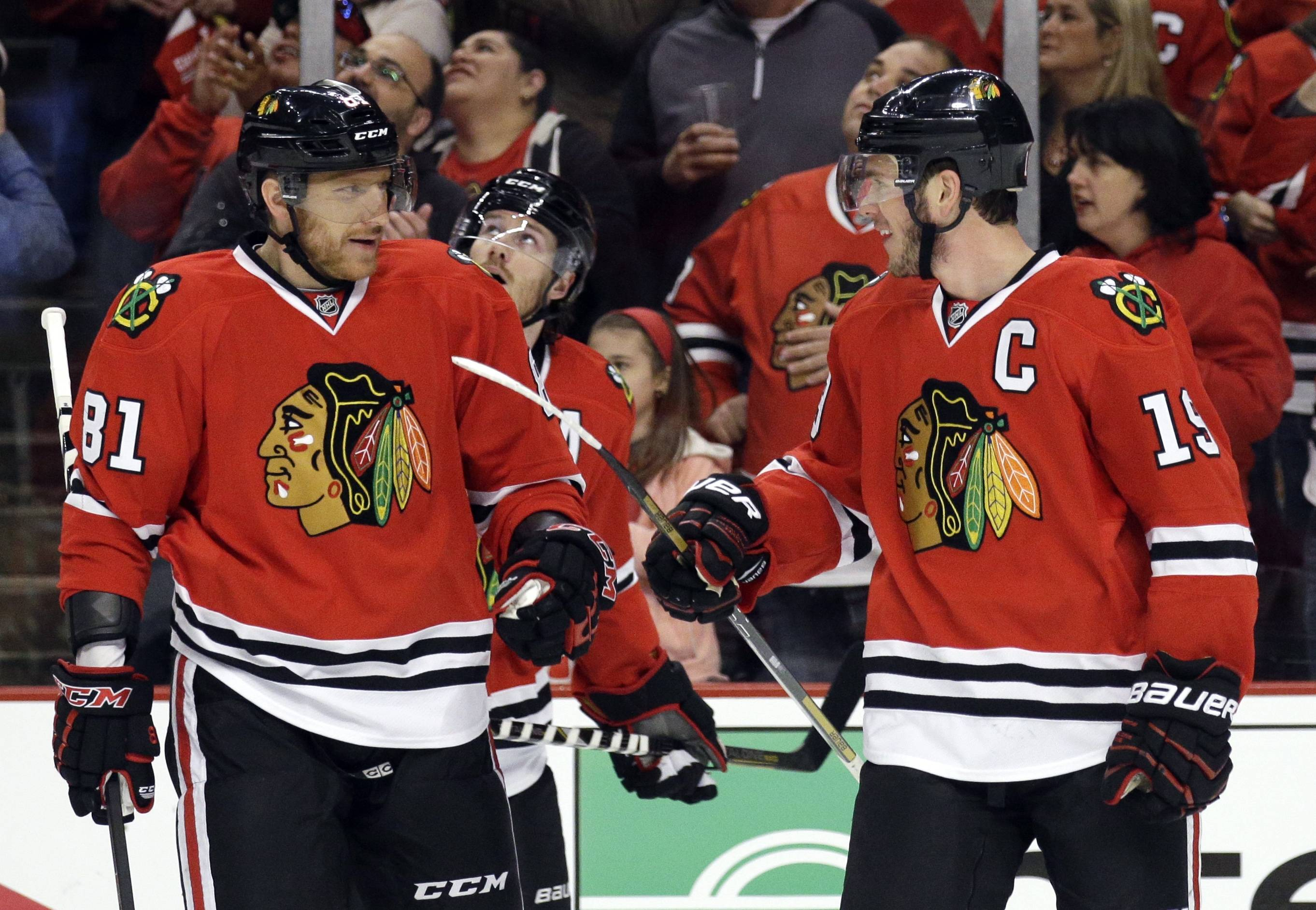 Chicago Blackhawks' Jonathan Toews (19), right, smiles as he celebrates with Marian Hossa (81) after scoring hi goal during the first period.