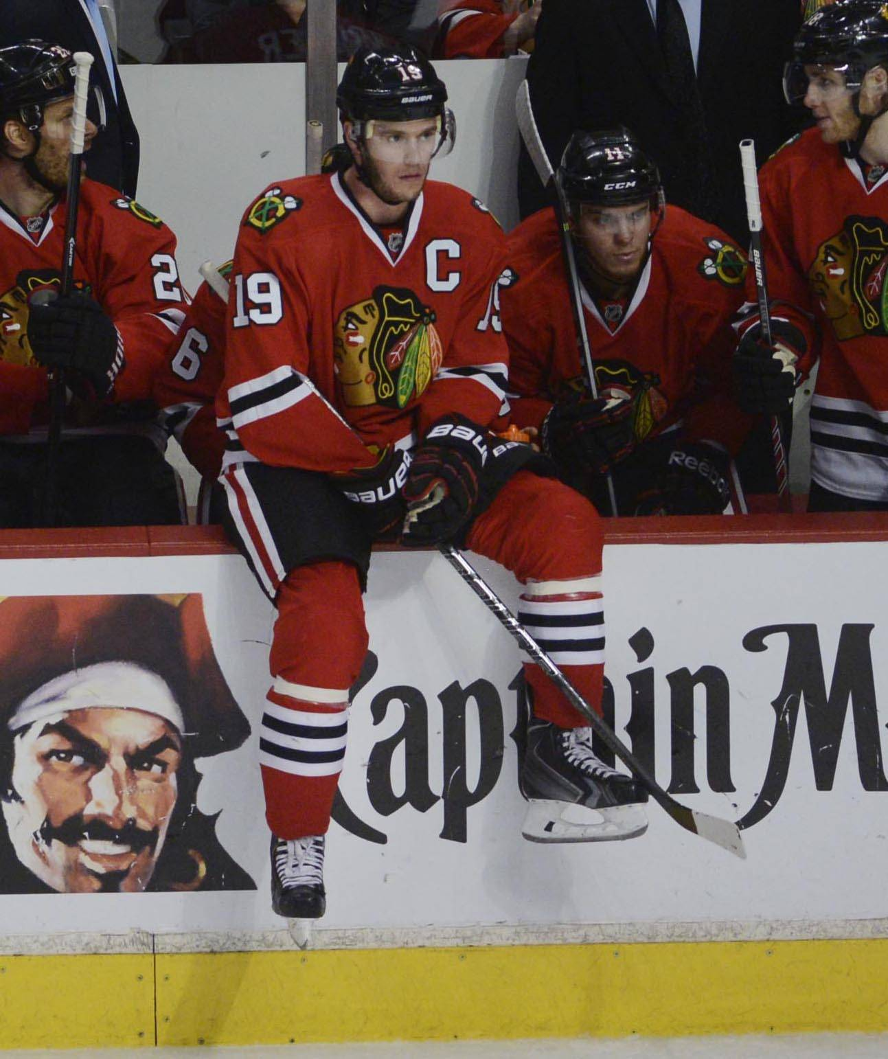 Chicago Blackhawks captain Jonathan Toews sits on the board in front of his bench during a time out against the Minnesota Wild.