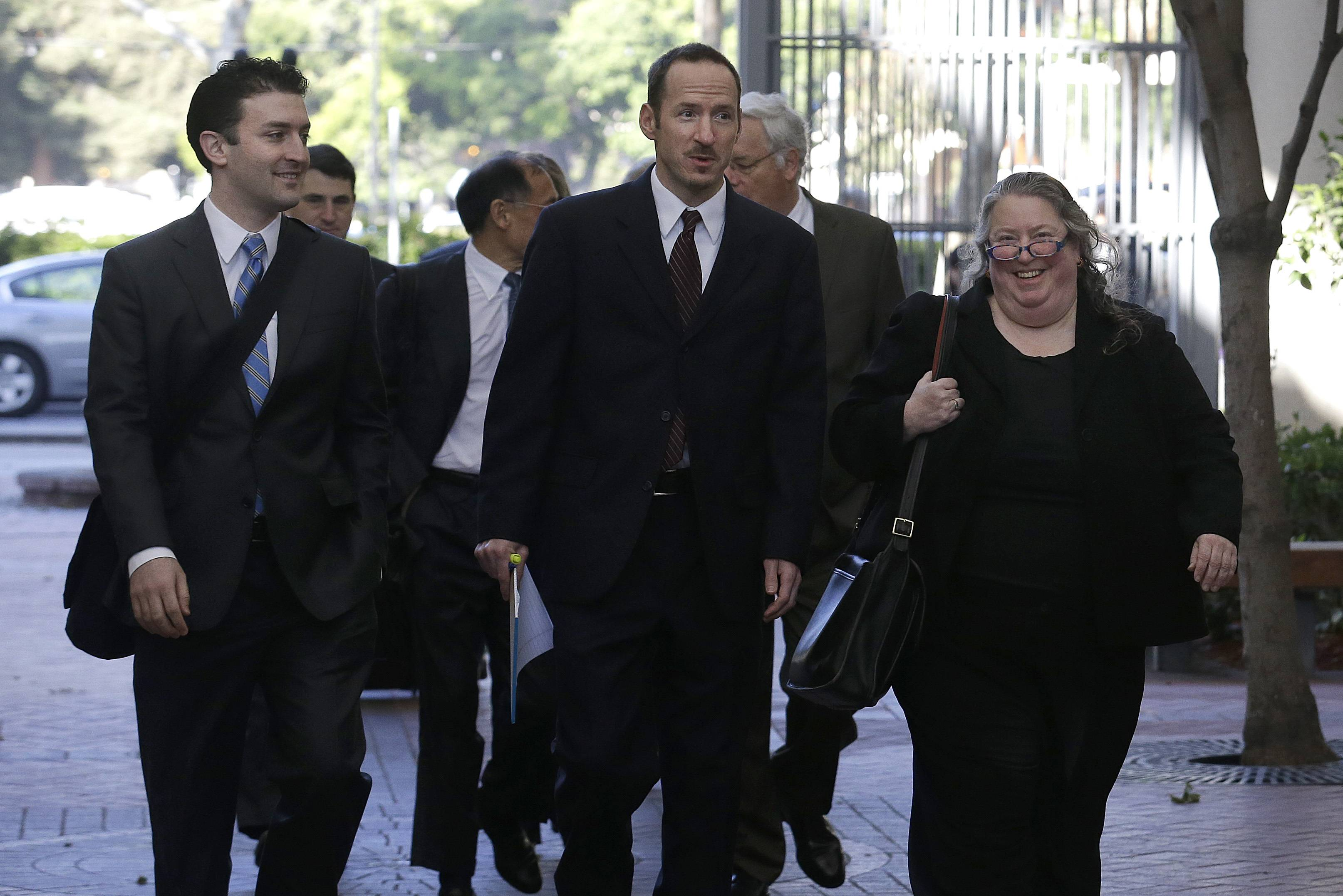 Apple attorney Rachel Krevans, right, walks with others to a federal courthouse in San Jose, Calif. A California jury determined Friday May 2, 2014, that Samsung infringed Apple smartphone patents and awarded $120 million damages.