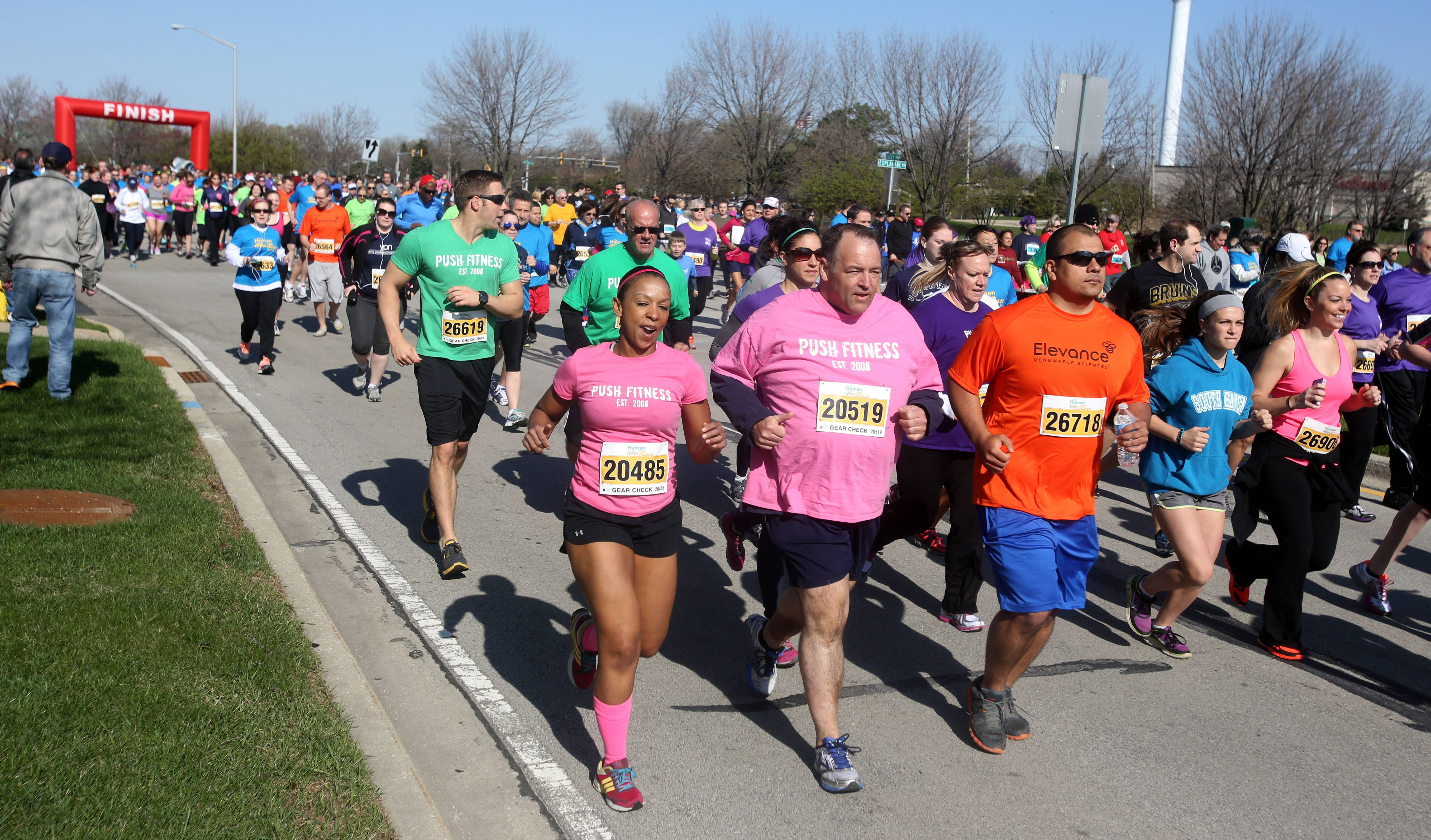With their trainers running alongside, Fittest Losers John Bohanek, in pink, and Chris Kalamatas, in green, power through the DuPage Human Race 5K Run.