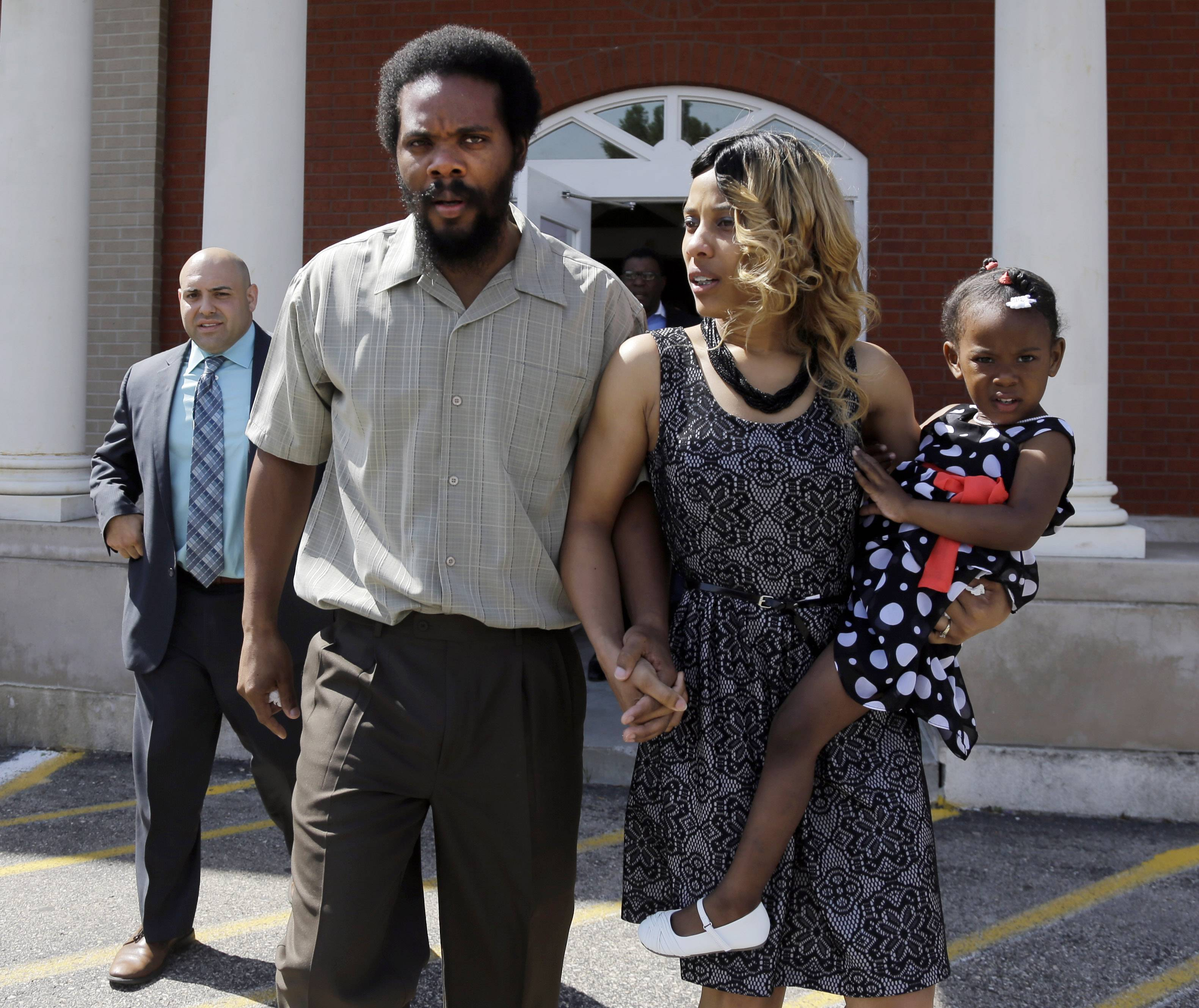 "Cornealious ""Mike"" Anderson walks out of the Mississippi County Courthouse along with his wife LaQonna, daughter Nevaeh, 3, after being released from custody, Monday in Charleston, Mo."