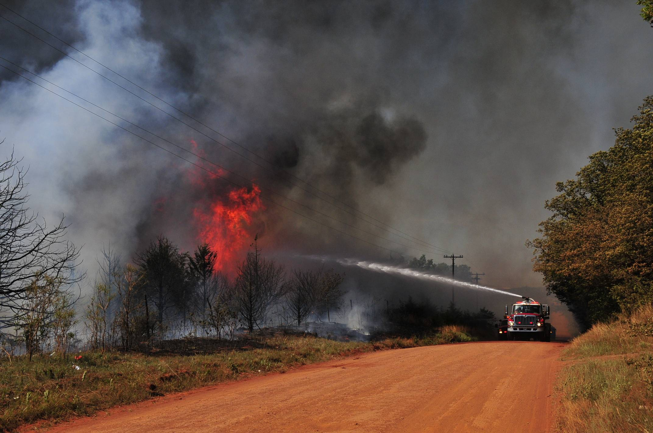 Firefighters work to extinguish a flare-up Monday in Guthrie, Okla. Gov. Mary Fallin declared a state emergency across Oklahoma after several wildfires broke out across the state, including a blaze north of Oklahoma City that destroyed at least a half dozen homes and left one man dead.