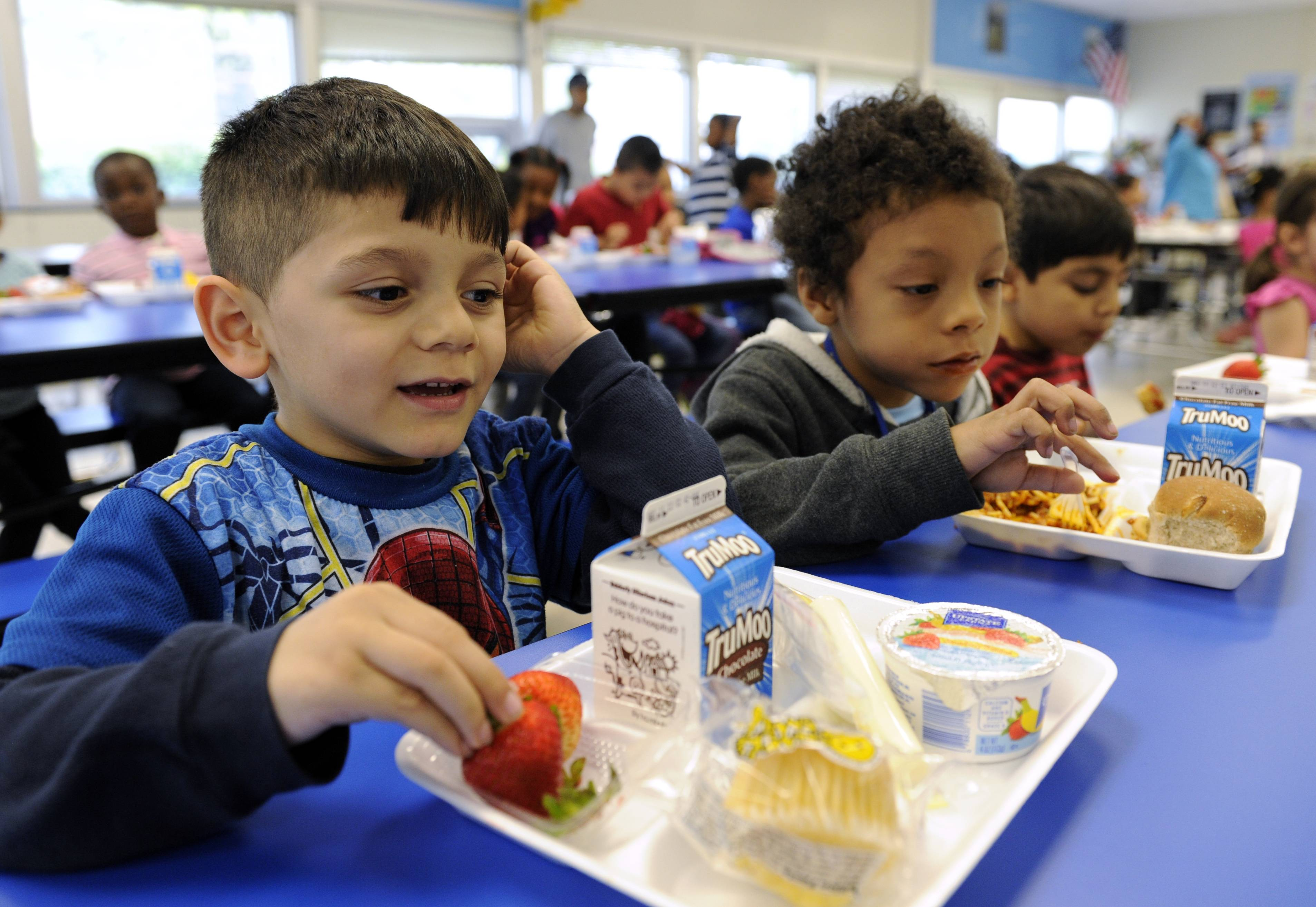 Biden Arias-Romers, 5, left, and Nathaniel Cossio-Boatwright, 6, eat lunch at the Patrick Henry Elementary School in Alexandria, Va. Starting next school year, pasta and other grain products in schools will have to be whole-grain rich, or more than half whole grain. The requirement is part of a government effort to make school lunches and breakfasts healthier.