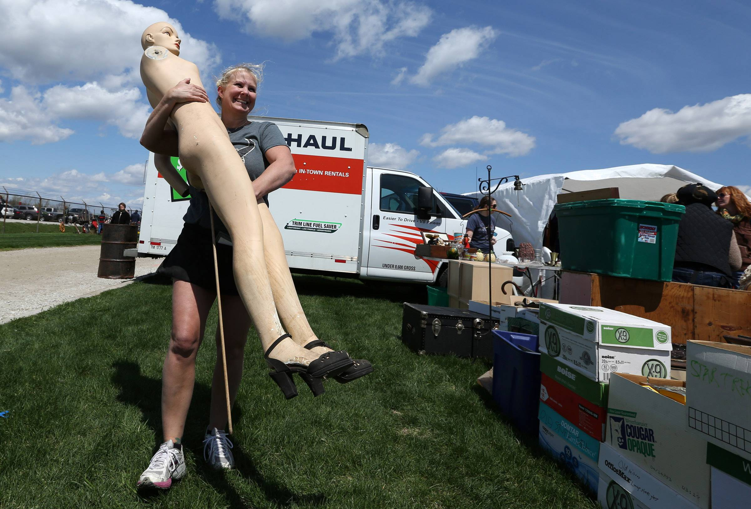Cheri Blockinger, of Naperville, puts a mannequin in place just before noon when the Kane County Flea Market at the fairgrounds opened on Saturday in St. Charles.