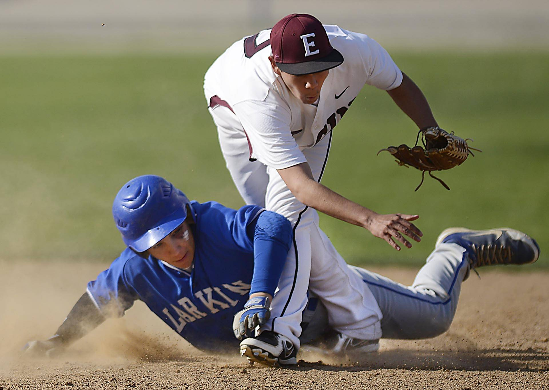 Trying to break up a double play, Larkin's Dan Lenz slides over the ankle of Elgin's Eddy Ramos Monday at Trout Park in Elgin. Ramos turned the double play, throwing out Larkin's Tanner Gardon in the third inning. He fell to the ground but stayed in the game.