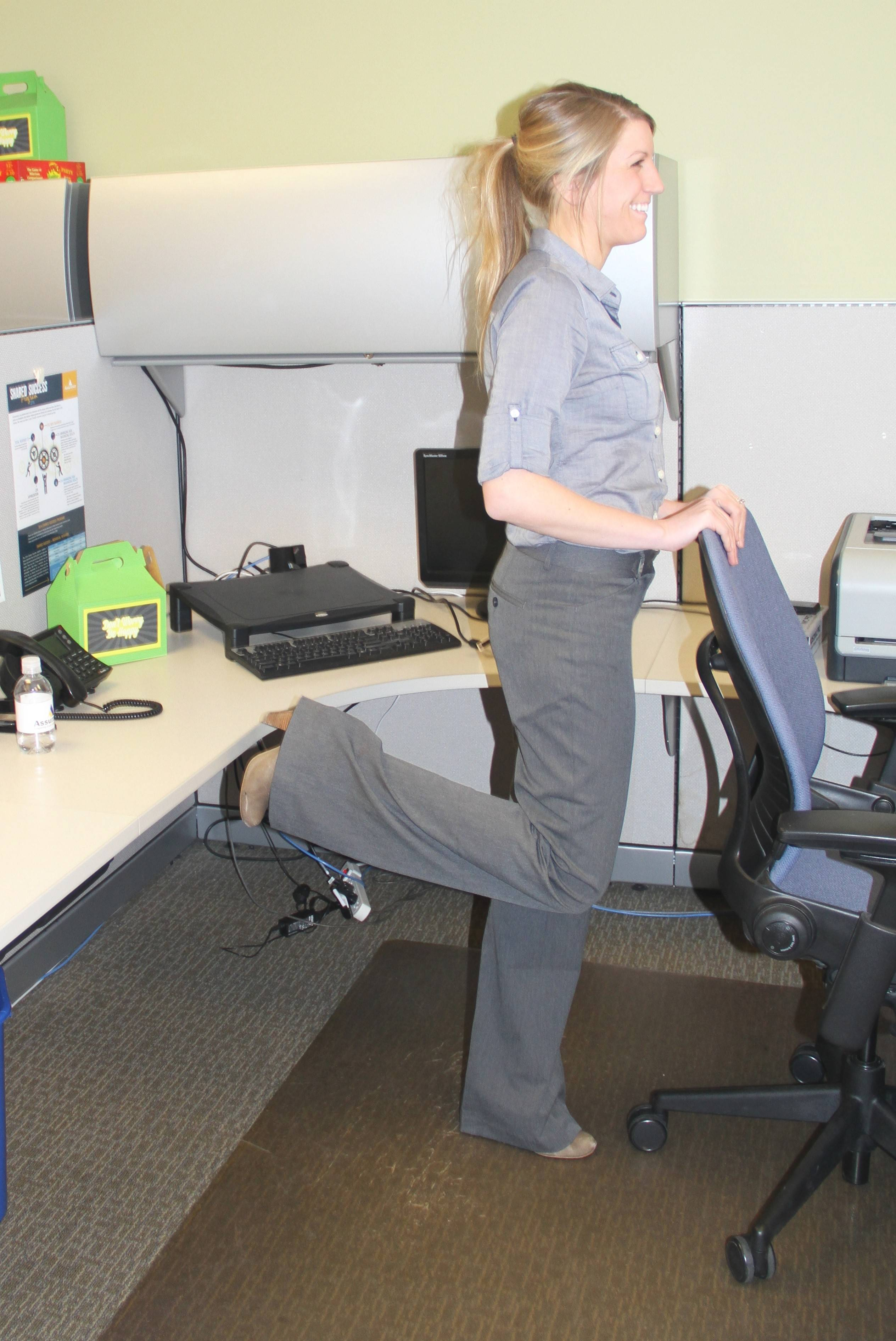 Jill Micklow, Wellness Specialist at Assurance, feels the burn as she does 10 reps of hamstring curls at her desk.