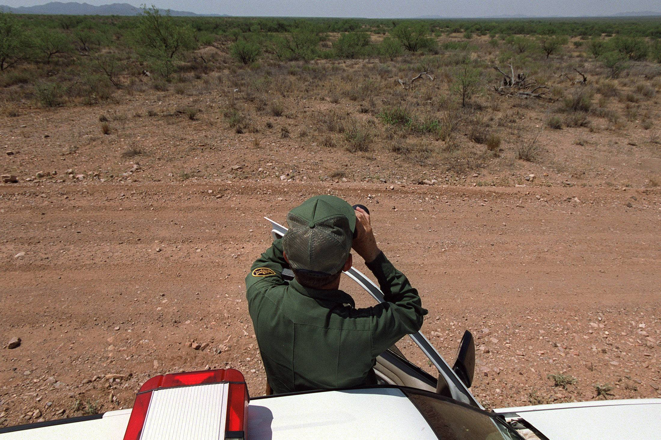 Senior border patrol agent Jorge L. Gonzalez scans the southern horizon of the Sonoran Desert in search of illegal immigrants who were spotted nearby. Gonzalez and other agents admit they are outmatched trying to spot every illegal immigrant in such a wide expanse of the Mexico/US border.