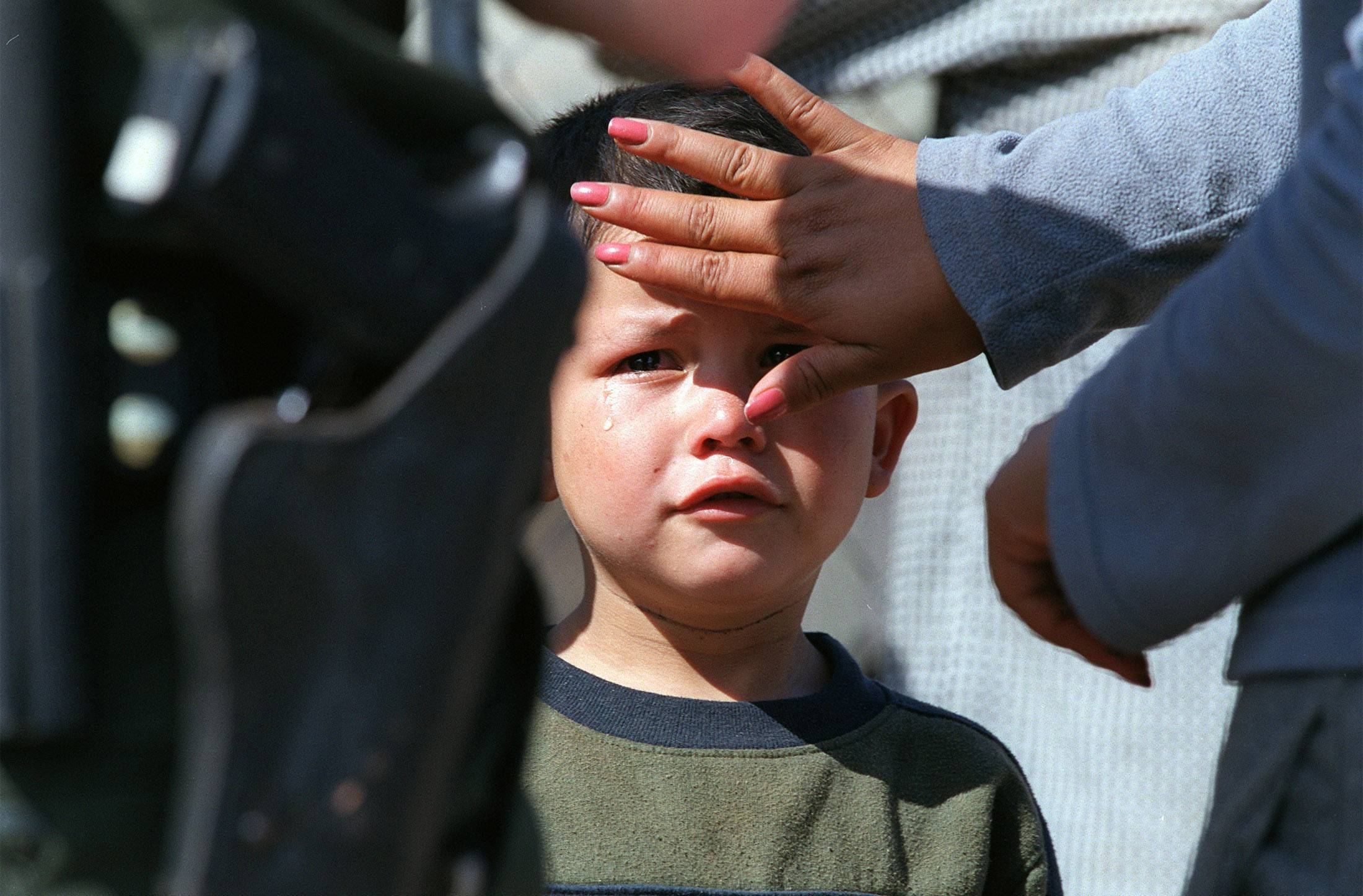 A young Mexican boy has tears wiped from his eyes by his mother as a U.S. border agent books them after finding them trying to illegally cross the border into Arizona.