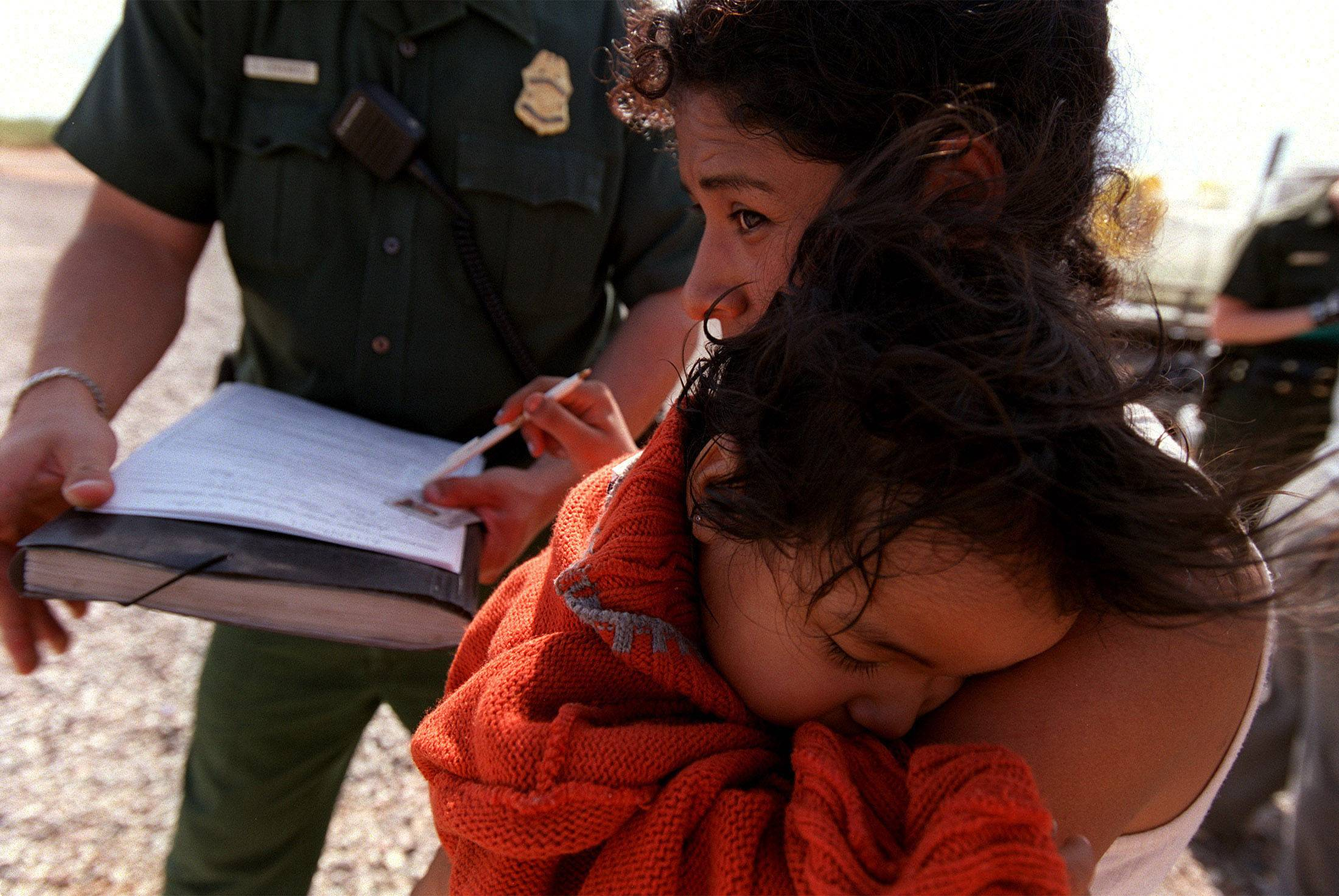 A Mexican woman cradles her listless daughter in her arms as a U.S. Border Patrol agent processes them for transport back to Mexico. The two were found stuffed in the small, metal toolbox compartment of a pickup truck along with 19 other illegals just a few miles north of the Arizona -- Mexico border. It was 102 degrees that day.