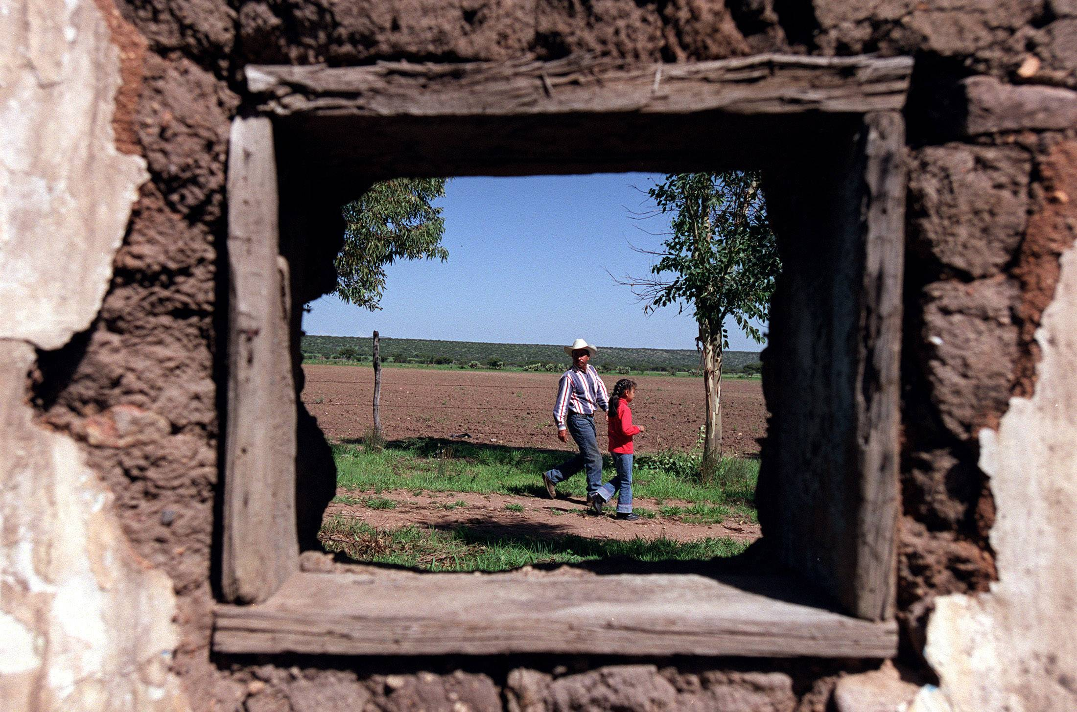 Antonio and Yesenia Martinez are framed by an old building on their ranch that was likely home to Palatine teacher Lupe Schoffstall during her early years in Zacatecas.