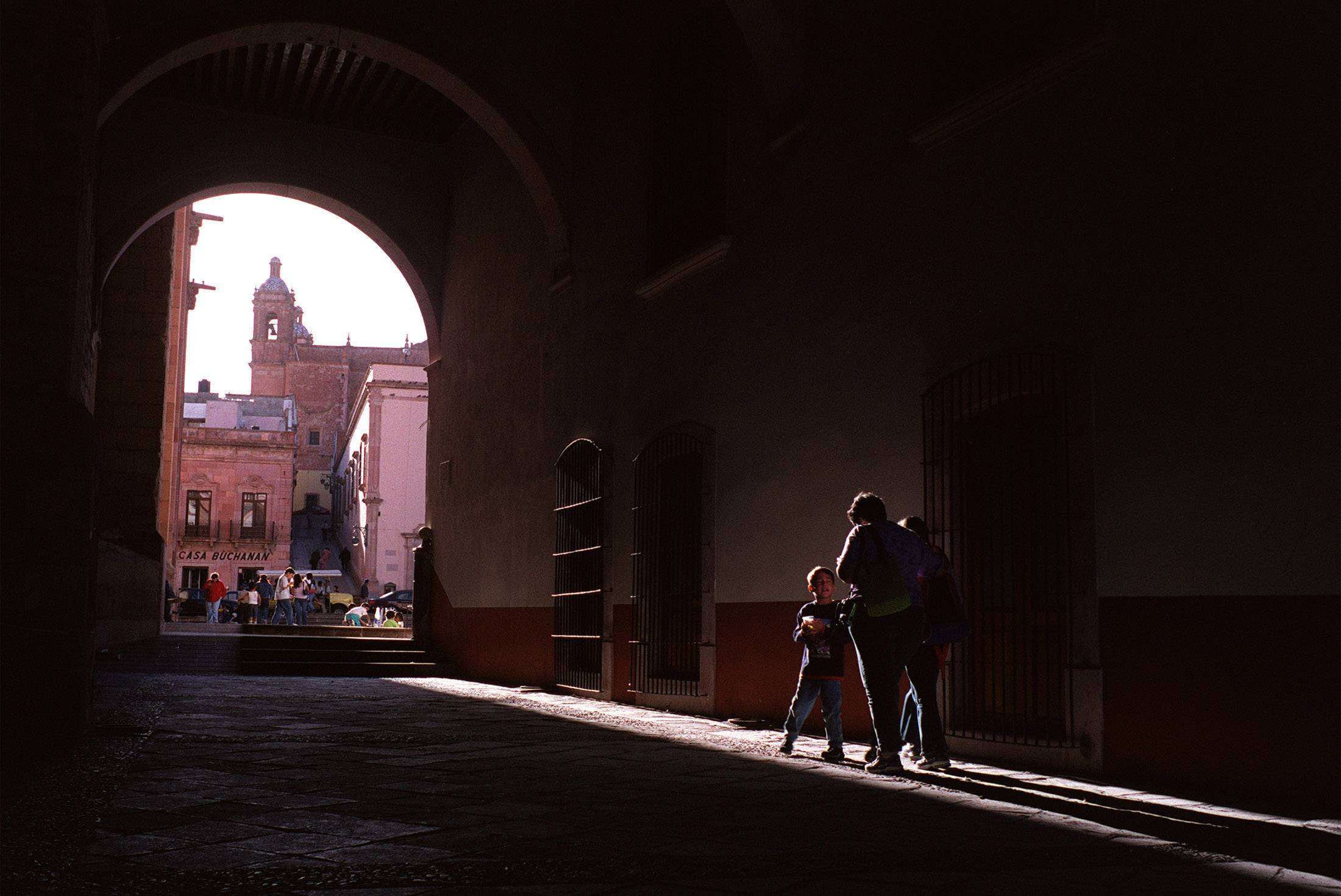 A mother and her children walk along a corridor in beautiful downtown Zacatecas as the evening sun lights their way.