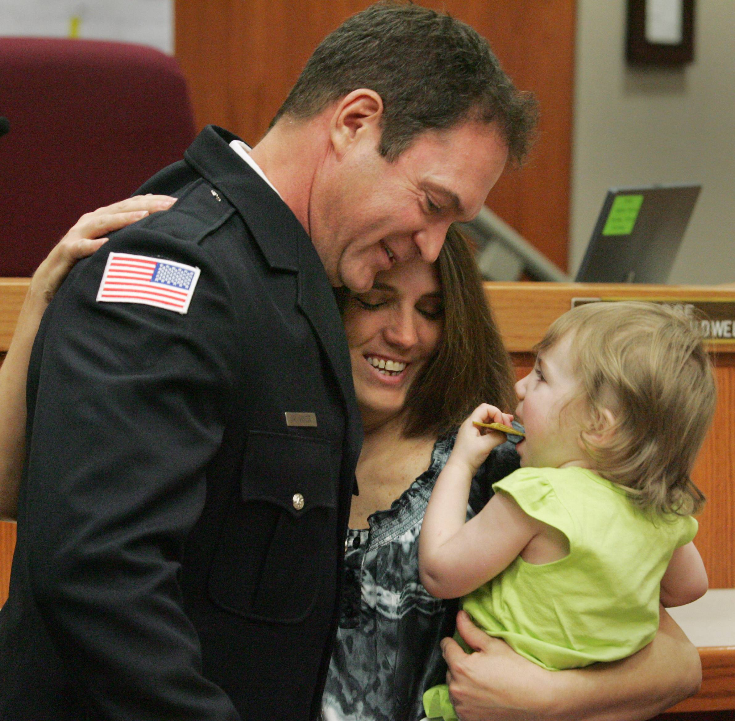 "Addison firefighter Joel ""Jay"" Arnier reunites with 20-month-old Kaitlyn Winoker and her mom, Trisha Schuler Friday at the McHenry County Government Center in Woodstock after Arnier received special recognition for rescuing Kaitlyn from the Fox River on May 11, 2011."
