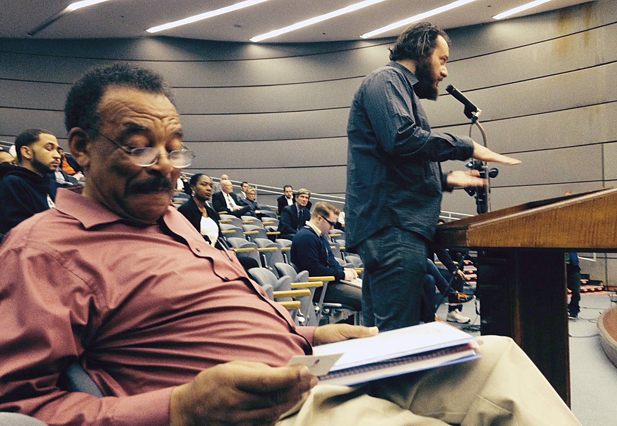 Ralph Wilson, left, looks at a business card he was handed after he testified at a public hearing on proposed rules for Illinois' new medical marijuana program on Monday in Chicago while would-be patient Steve Fix, right, speaks.