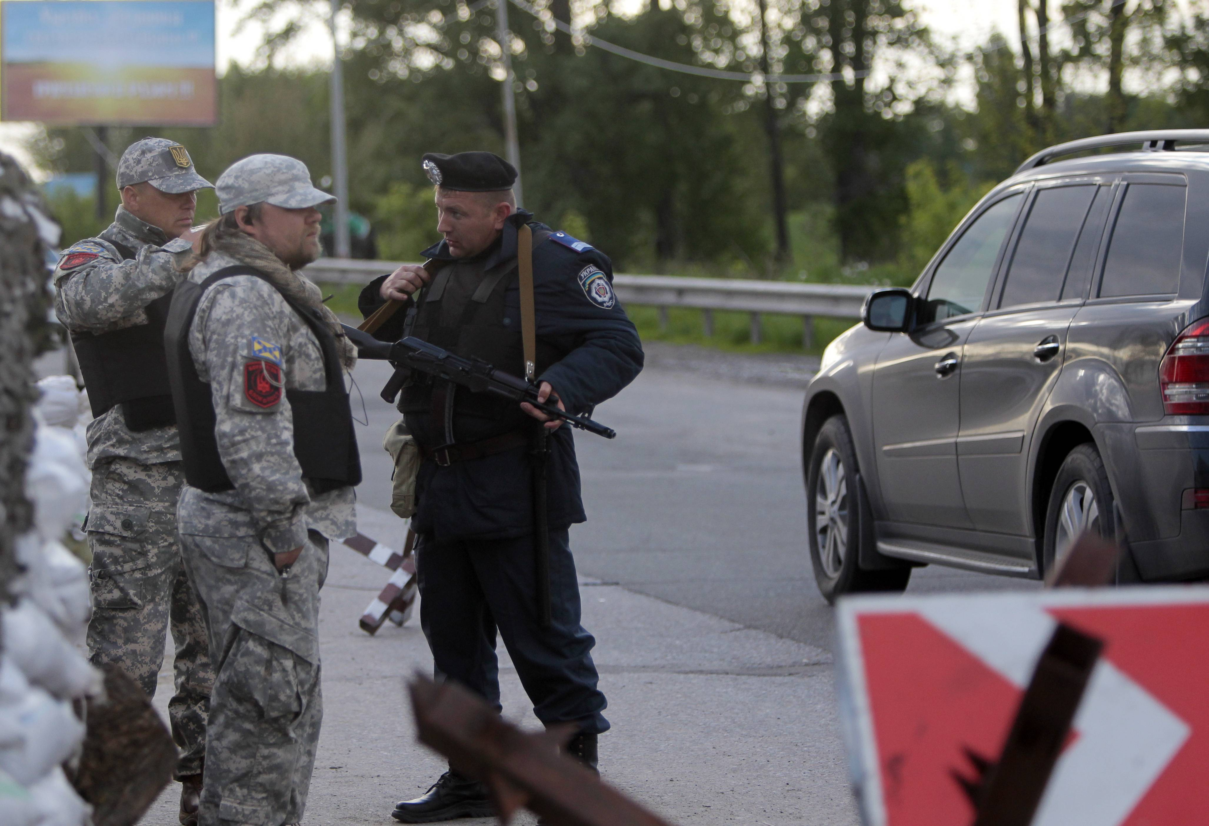 Men talk with policeman on the check point in Boryspil outside Kiev, Ukraine, Monday. Check points have been set up on roads leading to Kiev. The check points are manned by National Guard members and traffic police. They stop cars and buses to prevent terrorists, separatists and criminals from other regions from entering Kiev.